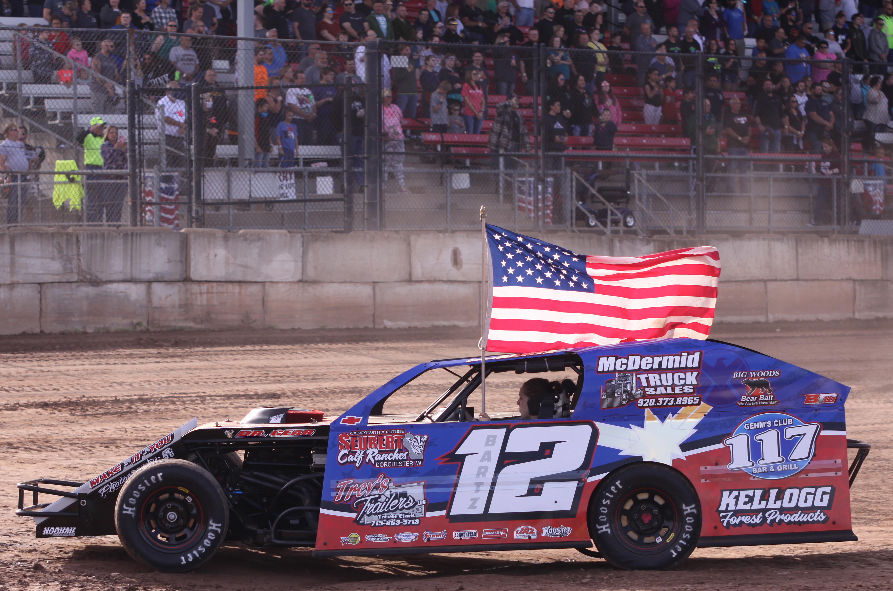 Jordan Bartz carries the U.S. flag as she drives around the track during the Shawano Speedway&#039;s season opener on Saturday. Drivers who won a 2019 title received the honor, with Bartz having won the IMCA Sport Mod class last summer.<br />Morgan Rode | NEW Media