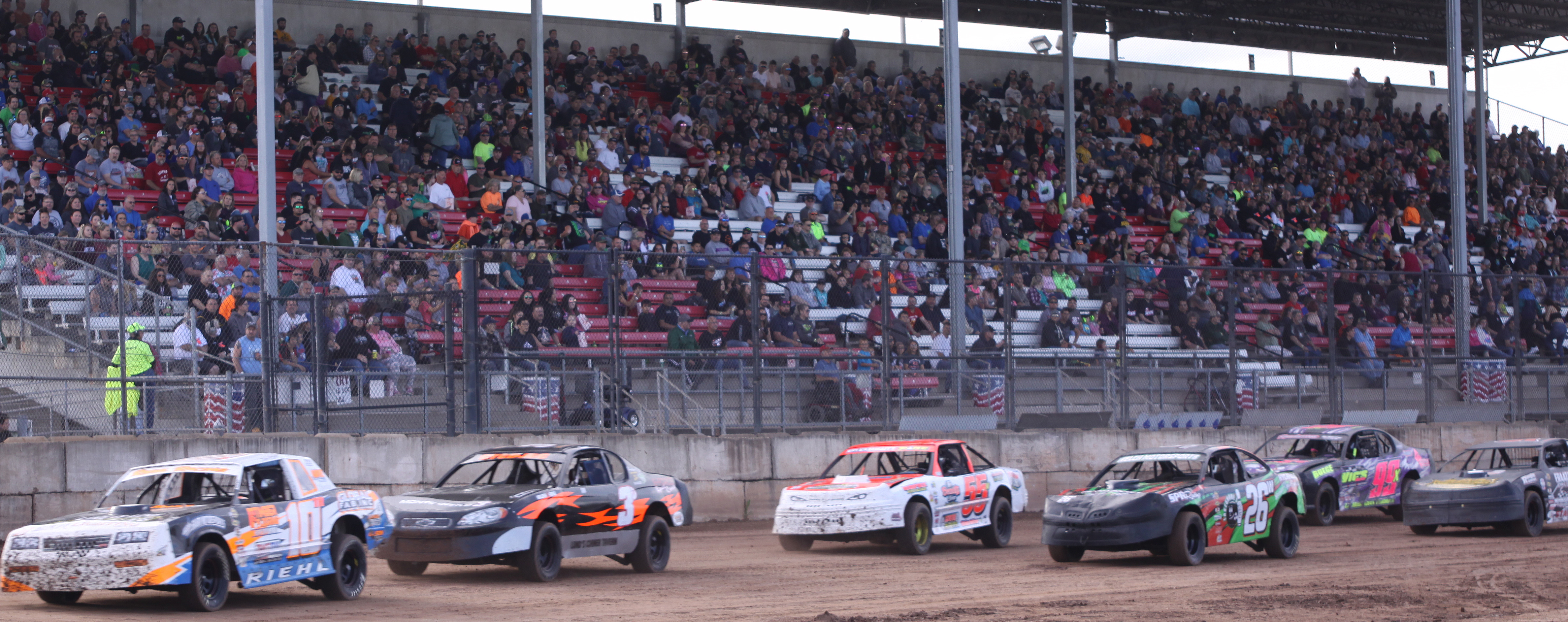 Tom Riehl (10), Dylan Stedjee (3), Shawn Wagner (55), Travis Welch (26) Jeremy Christians (99), Mitch Stankowski, right, compete in a IMCA Stock Car heat race in front of a packed grandstand at Shawano Speedway on Saturday.<br />Morgan Rode | NEW Media