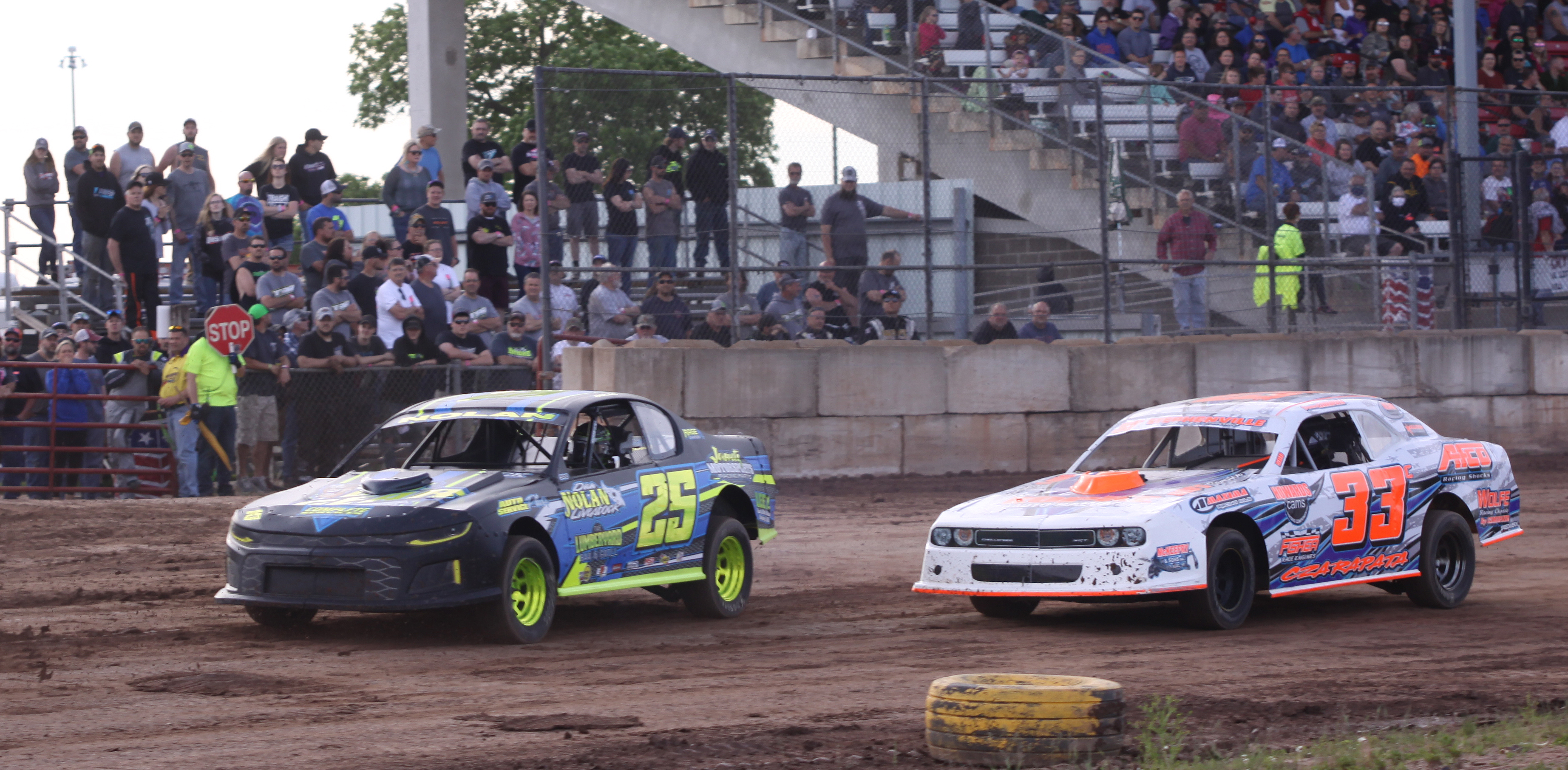 Trent Nolan (25) and Brandon Czarapata (33) head toward turn one during a IMCA Sport Mod heat race during Saturday&#039;s season opener at Shawano Speedway.<br />Morgan Rode | NEW Media