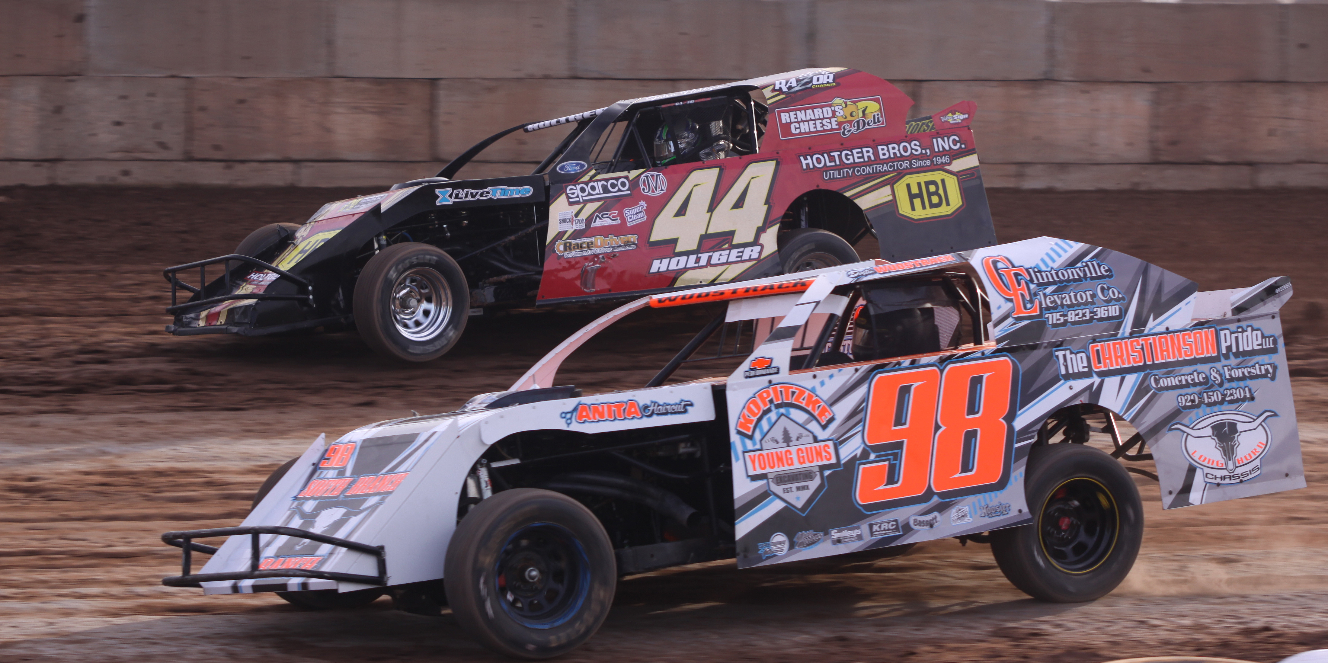 Dustin Wudstrack (98) and John Holtger (44) compete during an IMCA Sport Mod heat race during Saturday&#039;s season opener at Shawano Speedway.<br />Morgan Rode | NEW Media