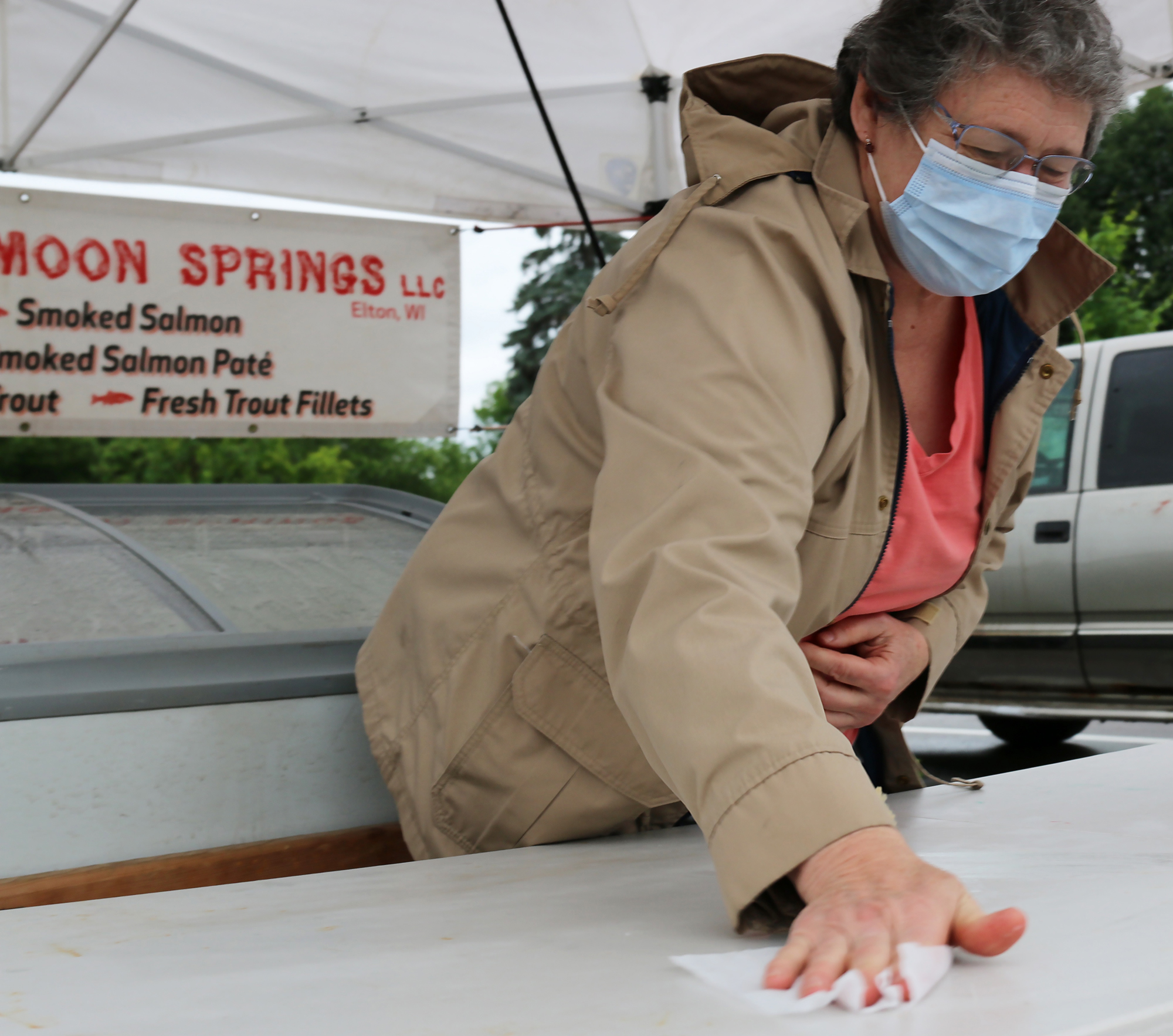 Bobbie Schneider of Silver Moon Springs wipes down her table after each customer at the first FRESH Project Farmers Market on Saturday. Most vendors wore masks and wiped down surfaces. Social distancing was not too much of an issue, given the repeated rain showers that limited the crowds.Carol Ryczek | NEW Media