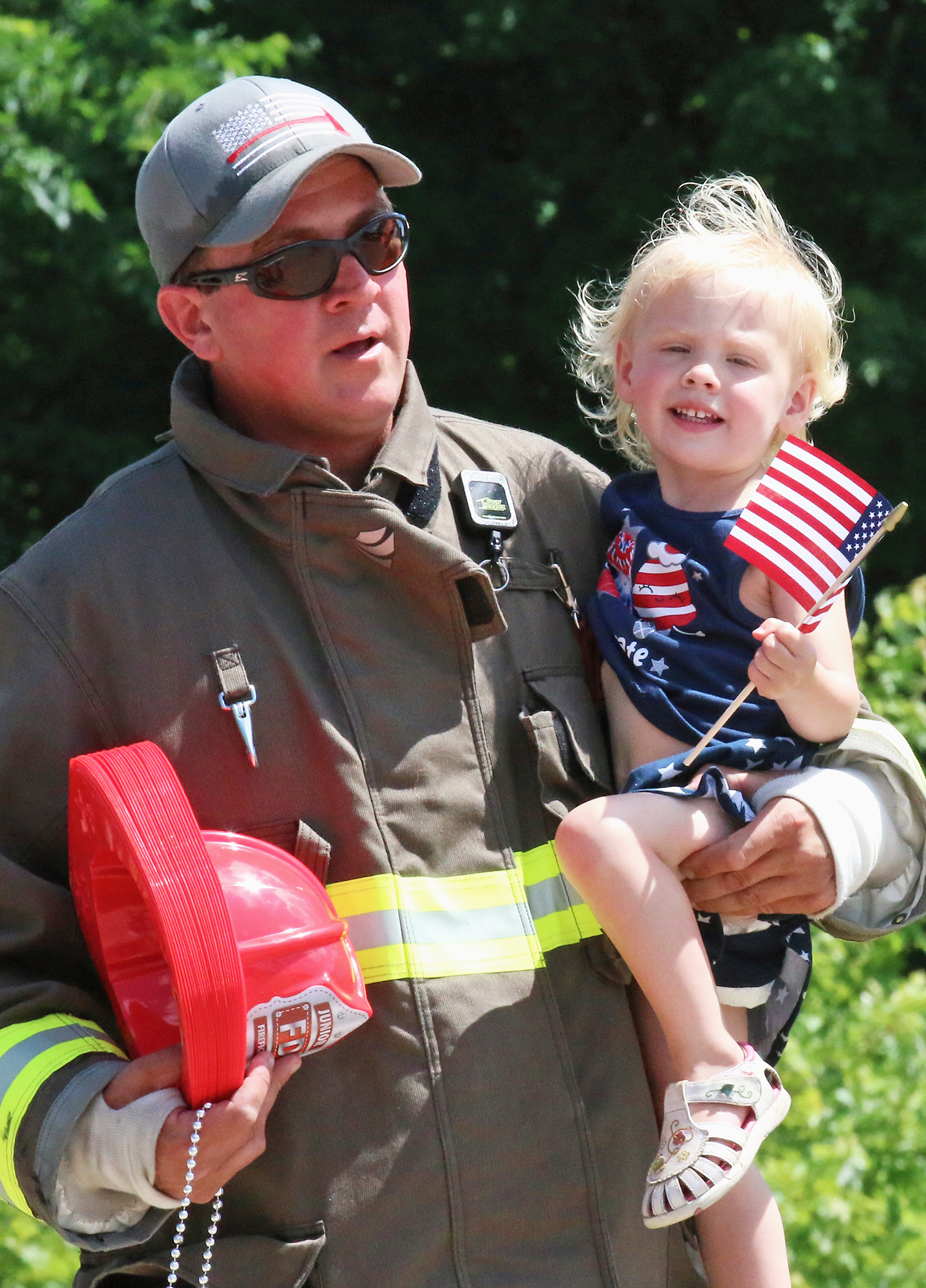 Shawn Hobbs helped daughter Holly Hobbs watch the parade after finishing their shift inside the Gresham Fire Department truck during the parade.Carol Ryczek | NEW Media
