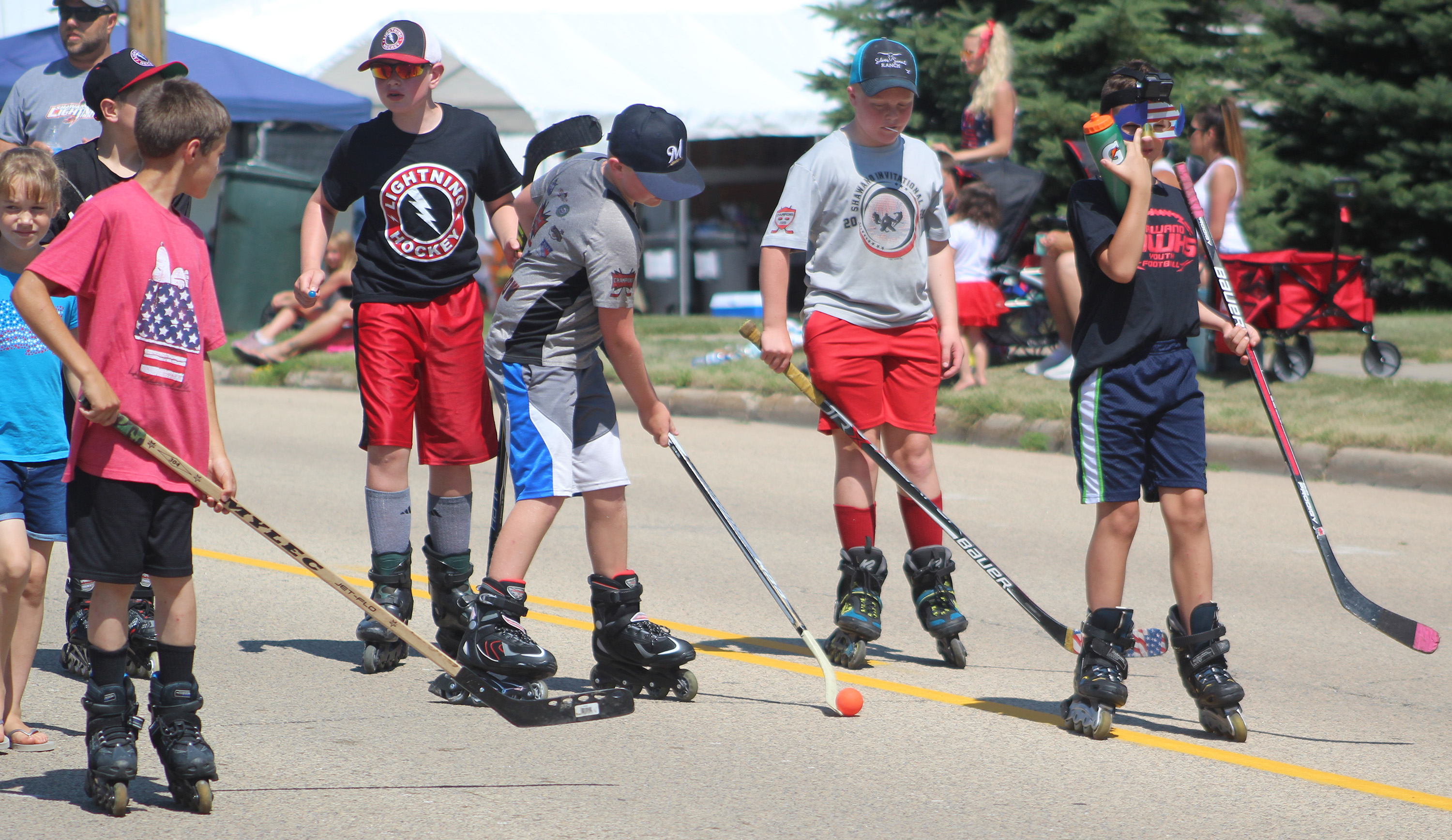 Youth members of the Shawano Hockey League show off their skills as they skate along the Independence Day parade route Saturday in Bonduel.Lee Pulaski | NEW Media