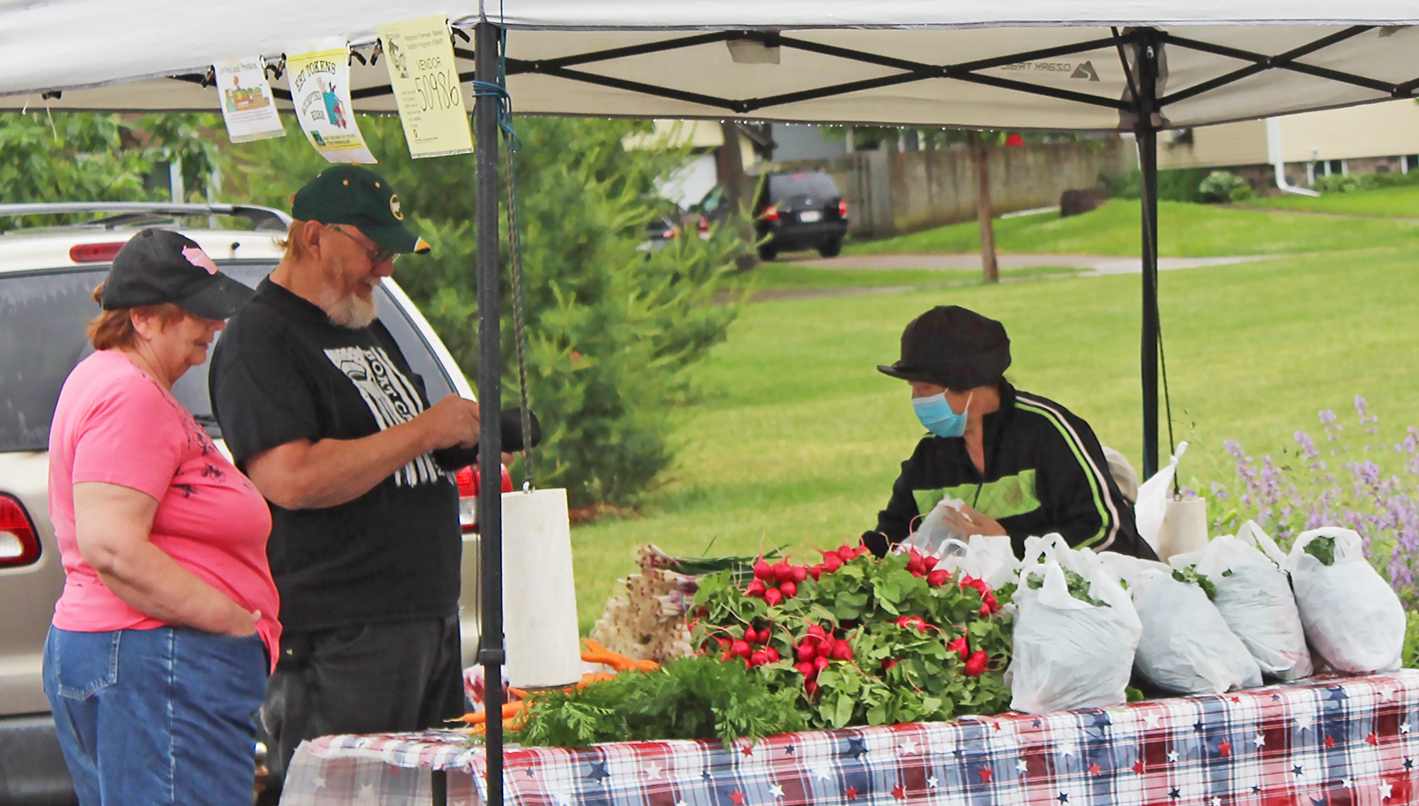 "Jolene and Peter Daniel, left, complete a purchase from Zoua Lee, right, on June 20 at the season's first Shawano Farmers Market at Franklin Park. Although the couple was called ""diehards"" by another vendor, Peter said, ""I just like all of the fresh veggies."" The farmers market will take place every Saturday through Oct. 3.David Wilhelms"