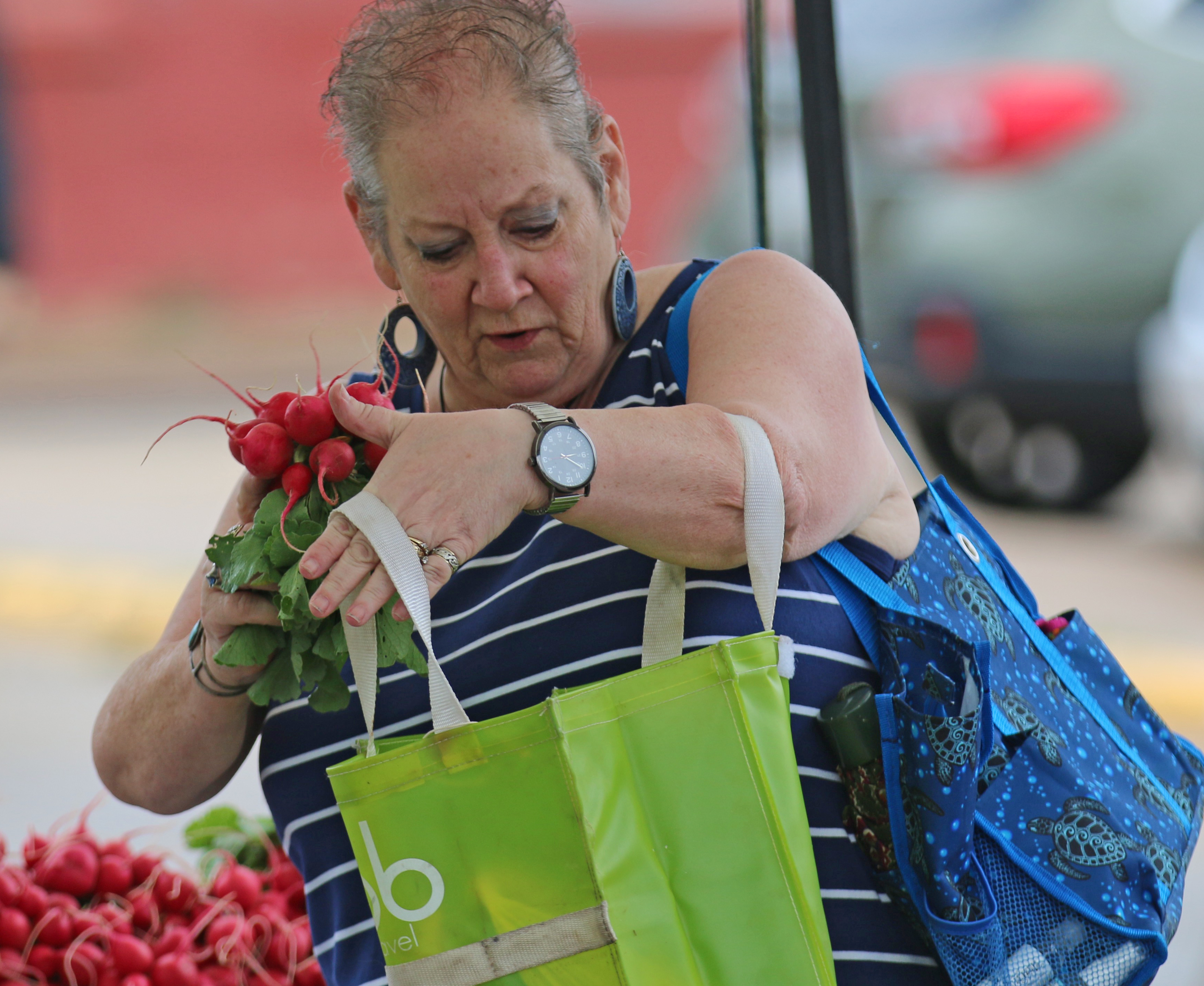Cindy Keuschel, a Loon Lake resident, selects radishes at the first Farmers Market of 2020 in Shawano. The market had regular attendees, according to the FRESH Project, new organizers of the market, despite the regular downpours Saturday morning.Carol Ryczek | NEW Media