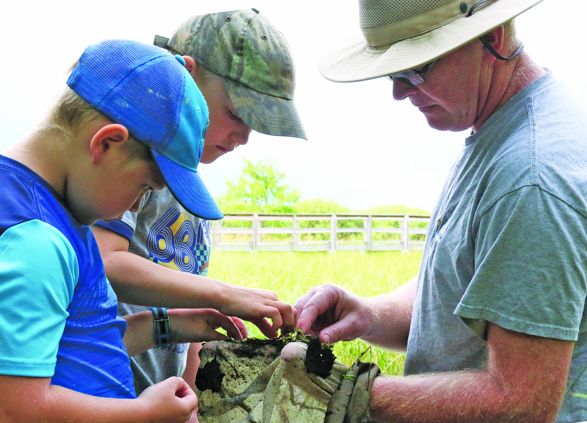 Jeremiah Hodges, left, and Evan Rankin help naturalist Tim Ewing sort through the leaves, mud, eggs, tadpoles and insects scooped from a swamp and pond area at the nature center.Carol Ryczek | NEW Media
