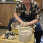 Olyvia Stark, a junior at Wittenberg-Birnamwood High School, holds her hands close together to help shape the wet clay that will become one of her bowls during a demonstration at the high school's Retrospective event May 5.  (Lee Pulaski   NEW Media)