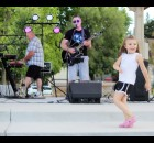 """Hailey Burtin, 4, of Shawano, was the only person to come up and dance at the request of the Fabulous Rugburns during the band's July 30 concert in Franklin Park, as band members John Groff, left, and Jon Perz perform """"Sweet Caroline."""" The band performs many songs from a variety of genres — rock, pop, country and even polka.  Lee Pulaski 