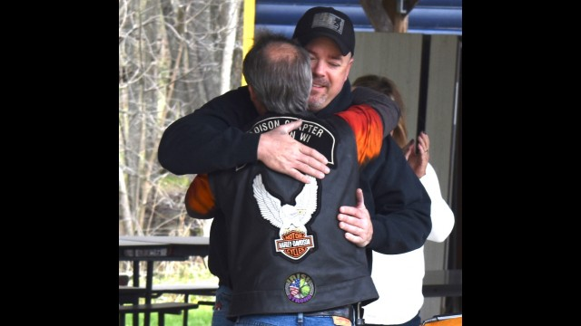 Navy veteran Shannon Flynn gets a hug from Kevin Thompson, president of Hogs for Heroes, after receiving a Harley-Davidson motorcycle from the nonprofit organization May 8 at Veterans Memorial Park in Suring. Warren Bluhm | NEW Media