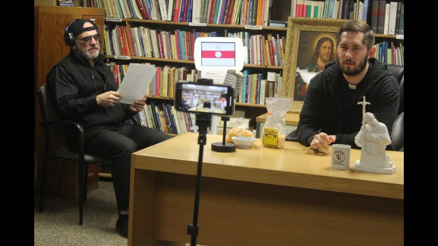 The Rev. Scott Valentyn, right, and Deacon Jim Lonick make a video to be uploaded on the Sacred Heart Catholic School's Facebook page Monday. The pair plans to do a humorous and educational segment every weekday during the coronavirus pandemic to keep connected with students, and they're considering doing occasional funny bits once restrictions are lifted.  Lee Pulaski   NEW Media