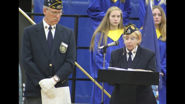 Cynthia Winkler, a member of American Legion Post 217, reads the list of Bonduel-area veterans who have passed away while post commander Russell Boettcher looks on during a Veterans Day ceremony Monday at Bonduel High School.  (Lee Pulaski | NEW Media)