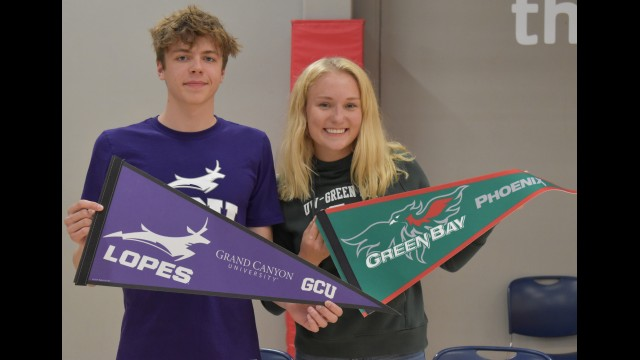 Wittenberg-Birnamwood's Wyatt Dickman, left, and McKenna Metropulos hold up flags for the colleges they will be swimming at during a signing event May 10 at the Woodson YMCA in Weston.  Andrea Metropulos