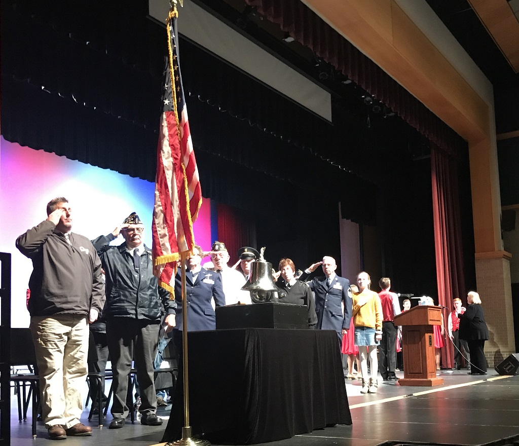 """Speakers salute the flag as Amy Thiel (background) conducts the Oconto Falls High School Vocal Jazz Ensemble in the national anthem, during the dedication program Saturday for the new community veterans monument. From left, Superintendent Dean Hess, American Legion Post 302 Commander Terris Umentum, Beverly Umentum, Vaughn Spaulding, Steve Magnin, Paula Gardipee, the Rev. Gary Olson and Madeline Maloney, a Washington Middle School student who read the poem """"I Am Your Flag."""" (Warren Bluhm 