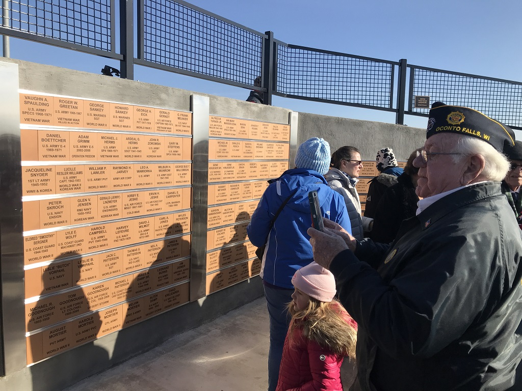 Gerald Linzmeyer, adjutant for Eick-Sankey American Legion Post 302, takes pictures of the new veterans monument after the dedication ceremony and formal flag-raising. (Warren Bluhm | NEW Media)