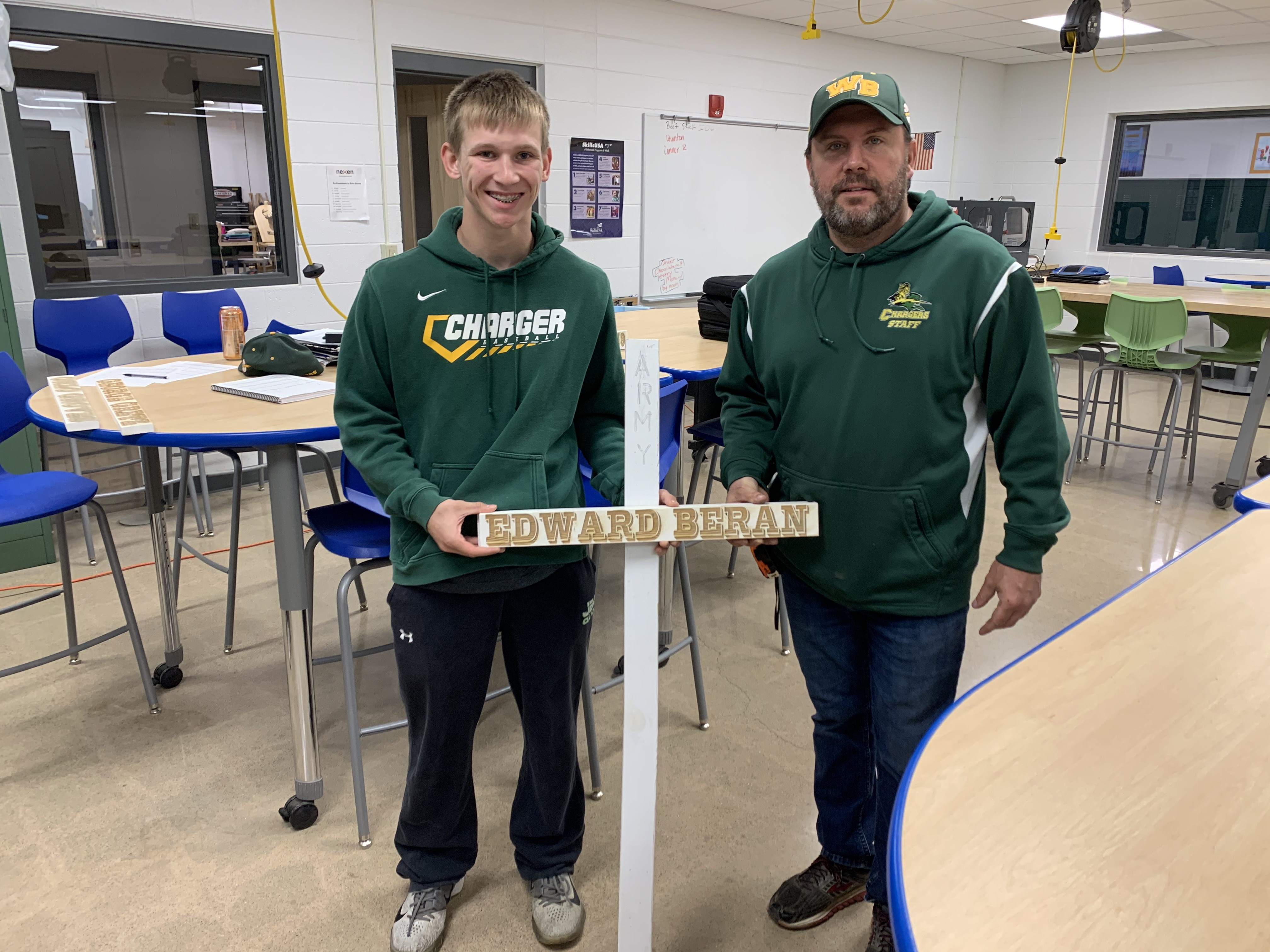 Wittenberg-Birnamwood High School senior Austin Worzella and Wittenberg-Birnamwood High School technology education teacher Waylon Resch display a model of what the crosses will look like when they are finished. The crosses will display the name of the veteran, what branch they served in and how many years they served.Luke Reimer | NEW Media