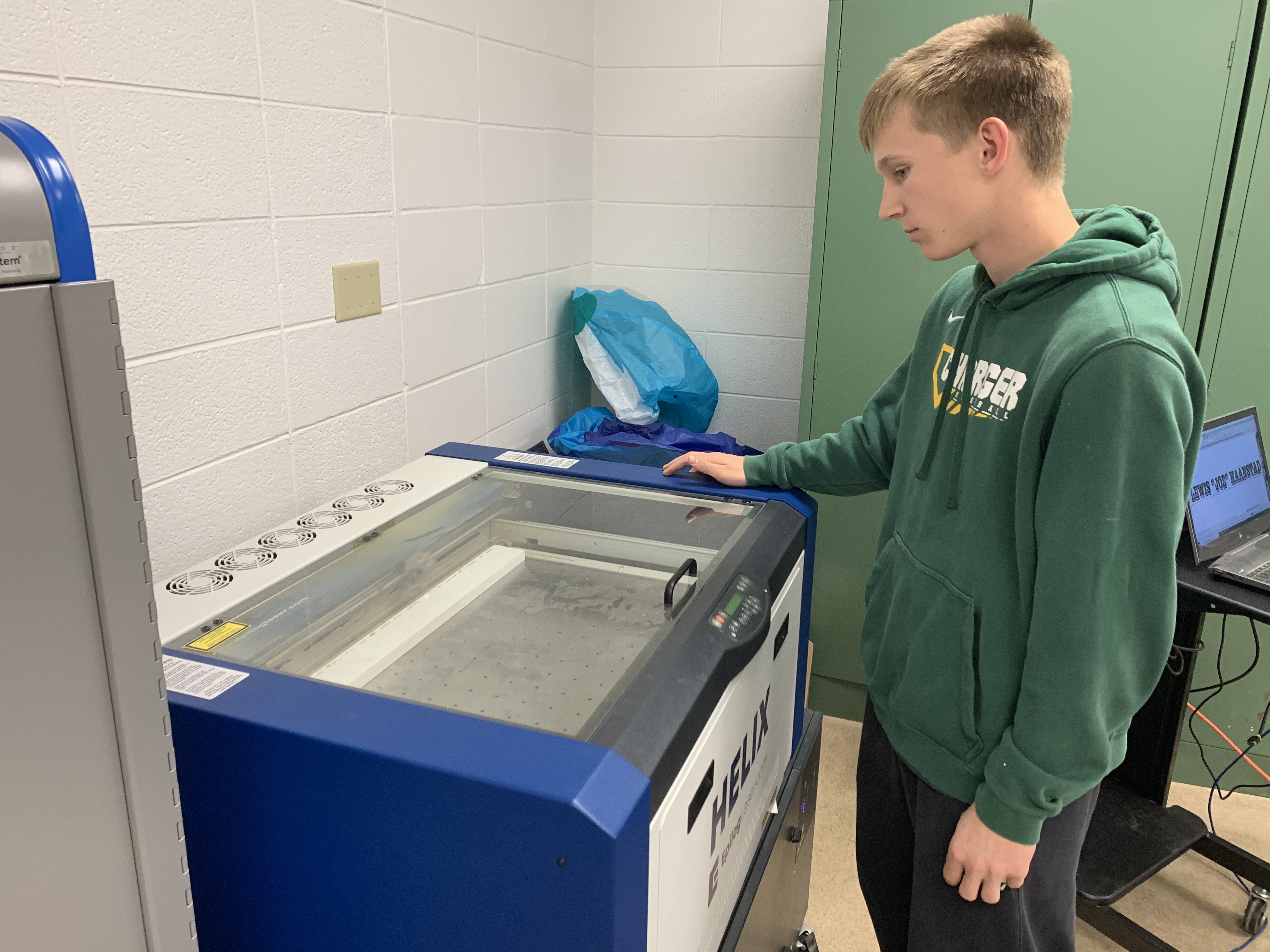 Wittenberg-Birnamwood High School senior Austin Worzella runs the laser printer May 7 that is used to display the names of the veterans. The crosses are created to memorialize the veterans who have passed away.Luke Reimer | NEW Media