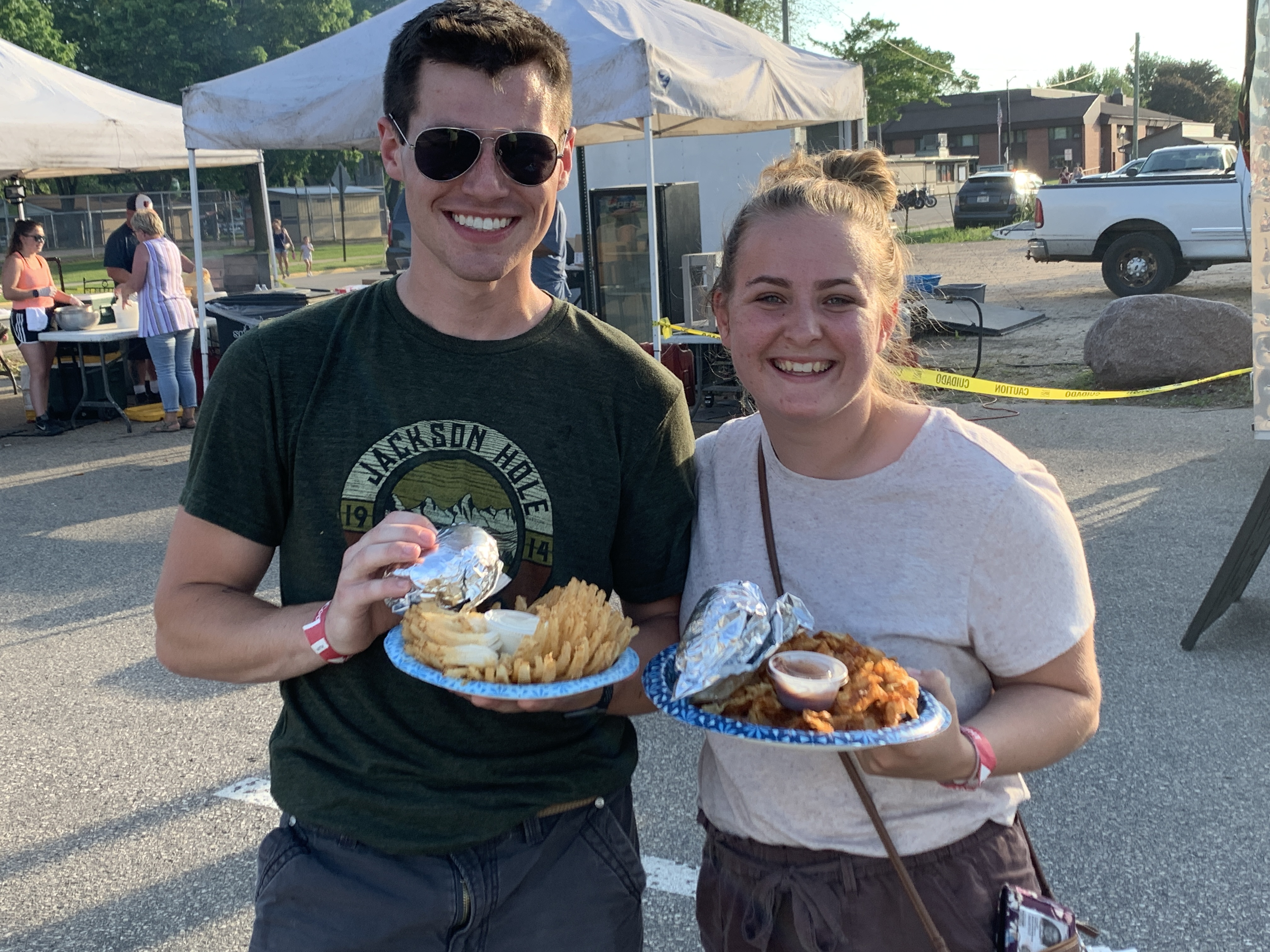From left, Shawano residents, Braxton Oroes and Emma Schmidt show off the food that they got from the various food trucks on site June 5. Oroes shows off his blooming onion, and Schmidt shows off her plate of french fries.Luke Reimer   NEW Media