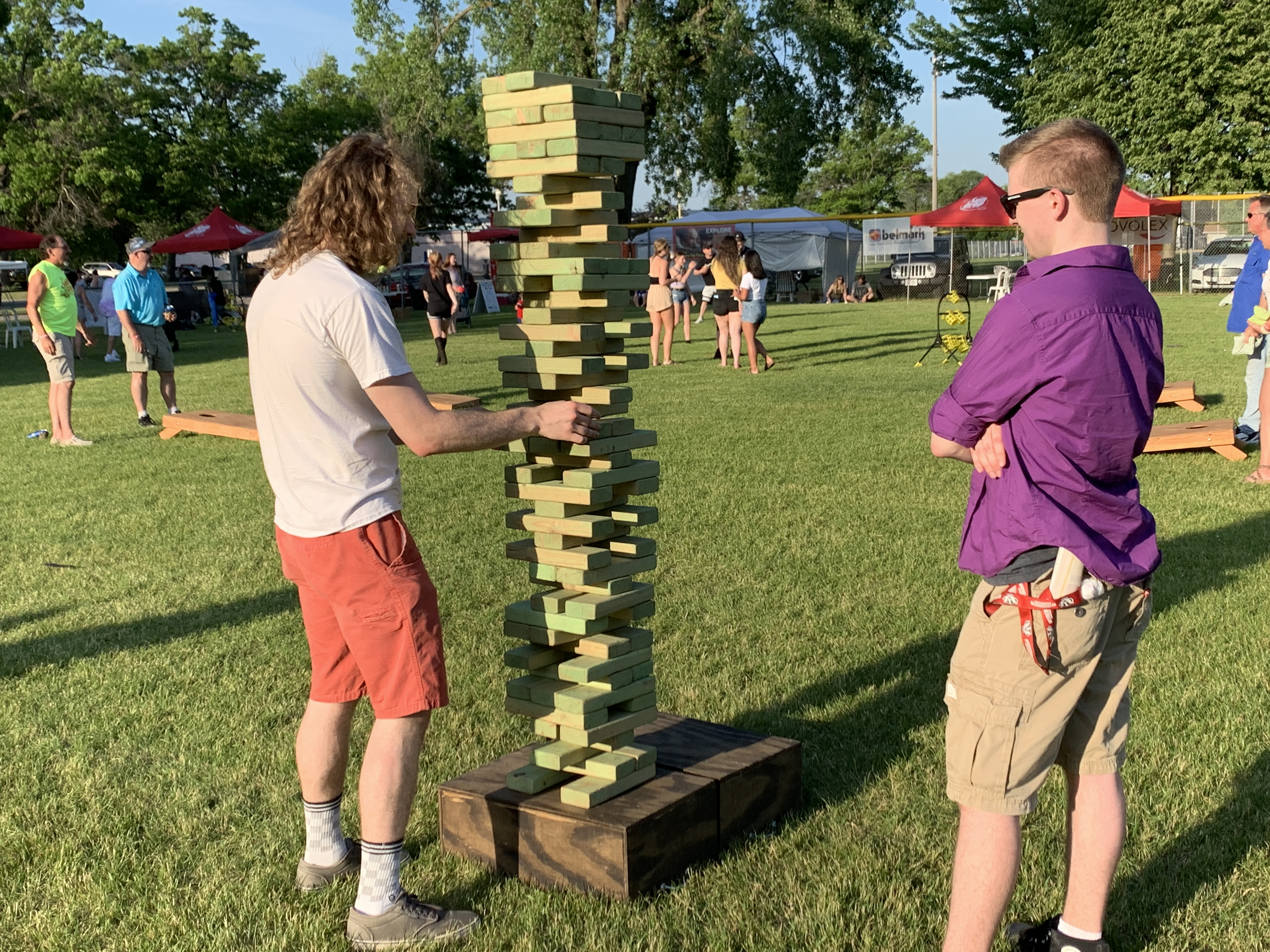 Quinn Hartzell, left, and Todd Weiss step away from the live music and the rest of the commotion to play a game of giant Jenga on June 5.Luke Reimer   NEW Media