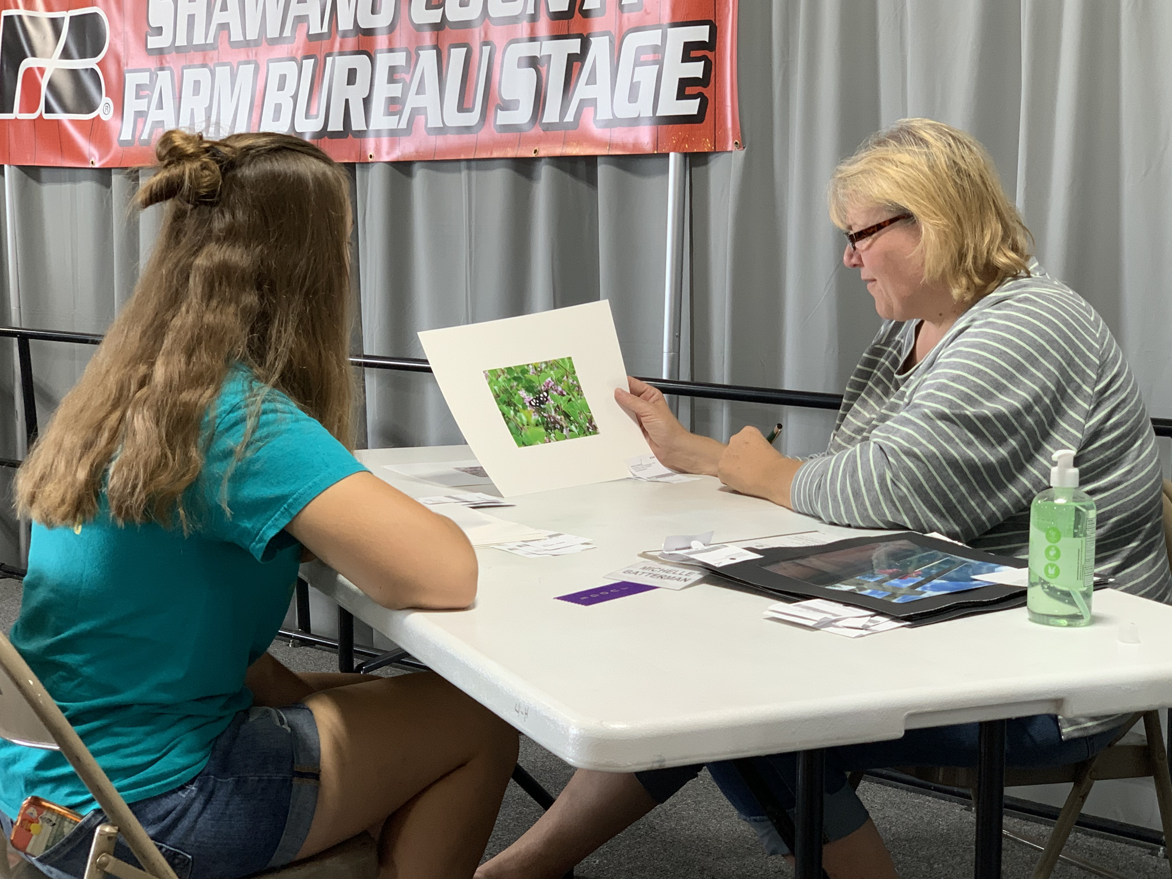 Heidi Dreyer from Landstad, left, gets judged Aug. 28 by Michelle Batterman on her photography piece of art at the 4-H barn on the Shawano Fairgrounds.(Luke Reimer   NEW Media)