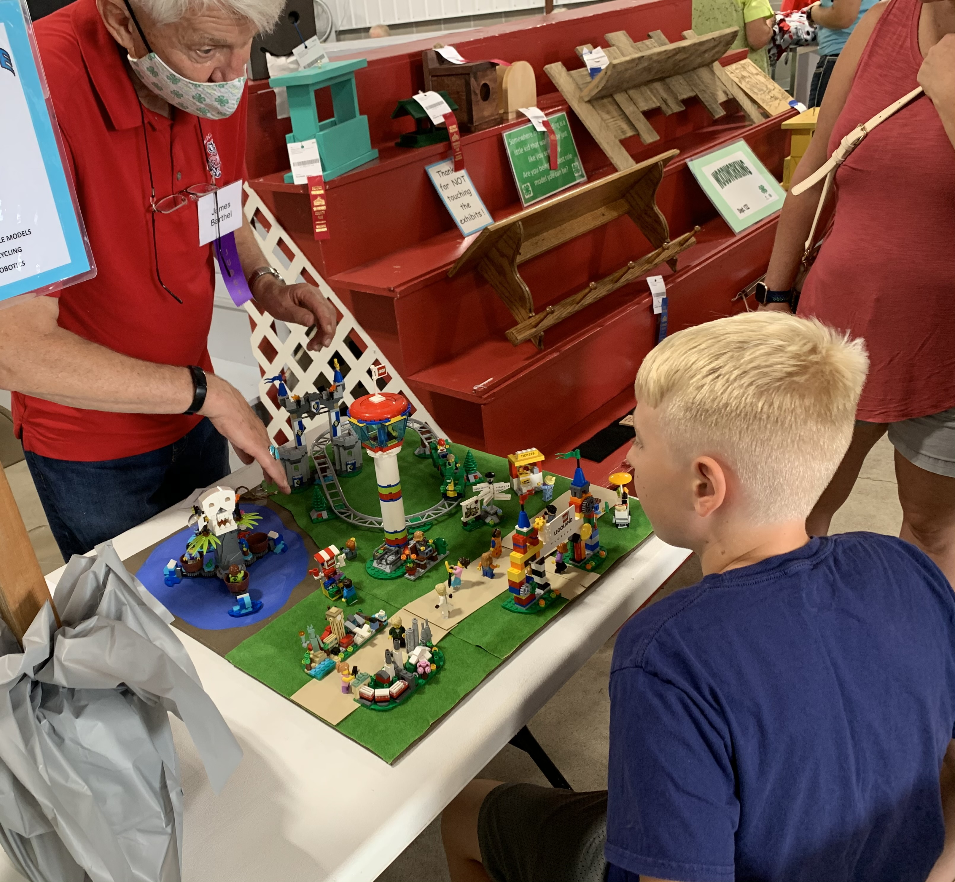 Judge James Barthel, left, examines Marion resident Lincoln Zillmer's Lego rendition of Florida's Legoland at the mechanical science and electricity booth in the Shawano Fairgrounds' 4-H barn Aug. 28.(Luke Reimer   NEW Media)