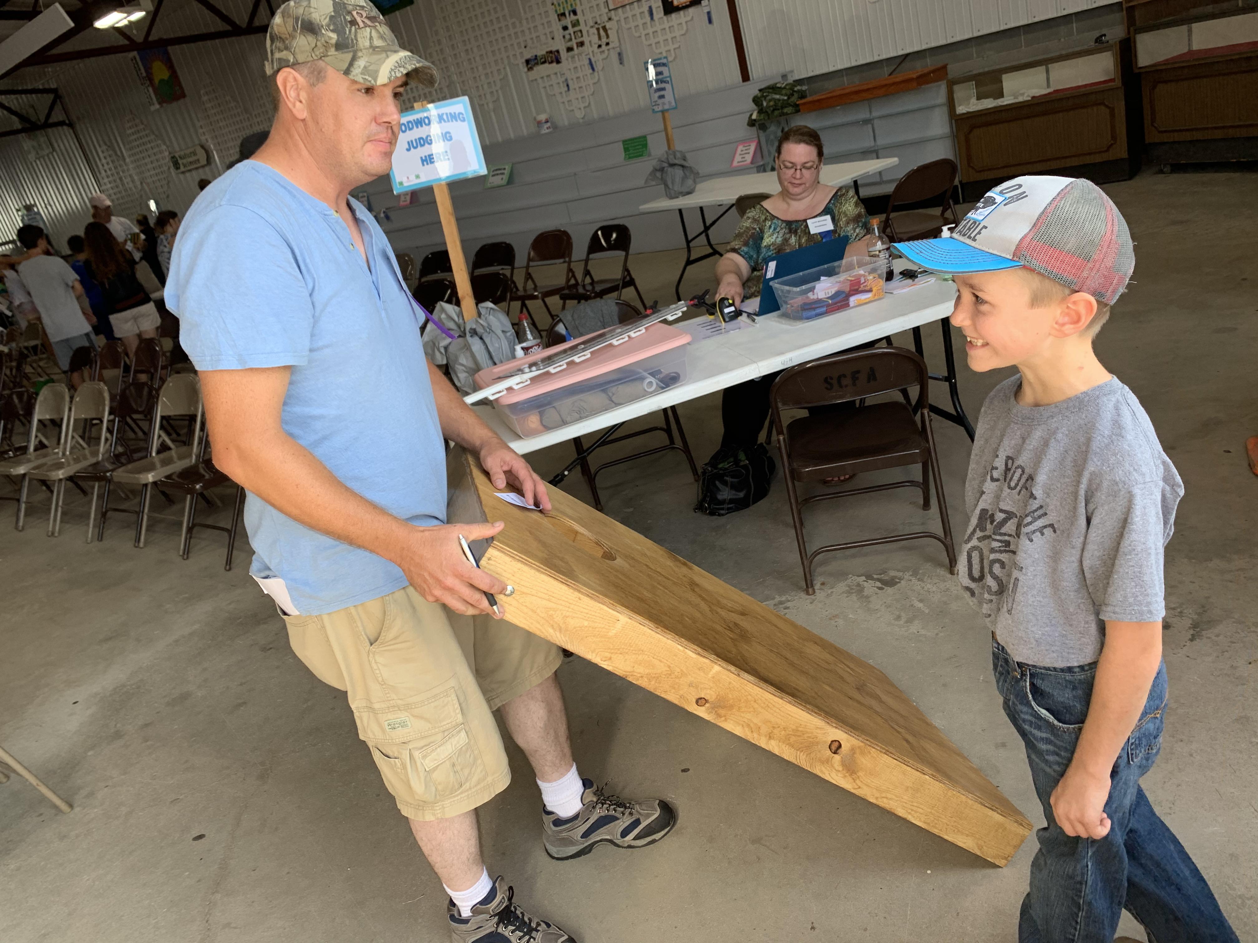 Judge David Bork, left, examines Cecil resident Trevor Bohn's bean bag board at the woodworking booth in the Shawano Fairgrounds' 4-H barn Aug. 28.(Luke Reimer   NEW Media)