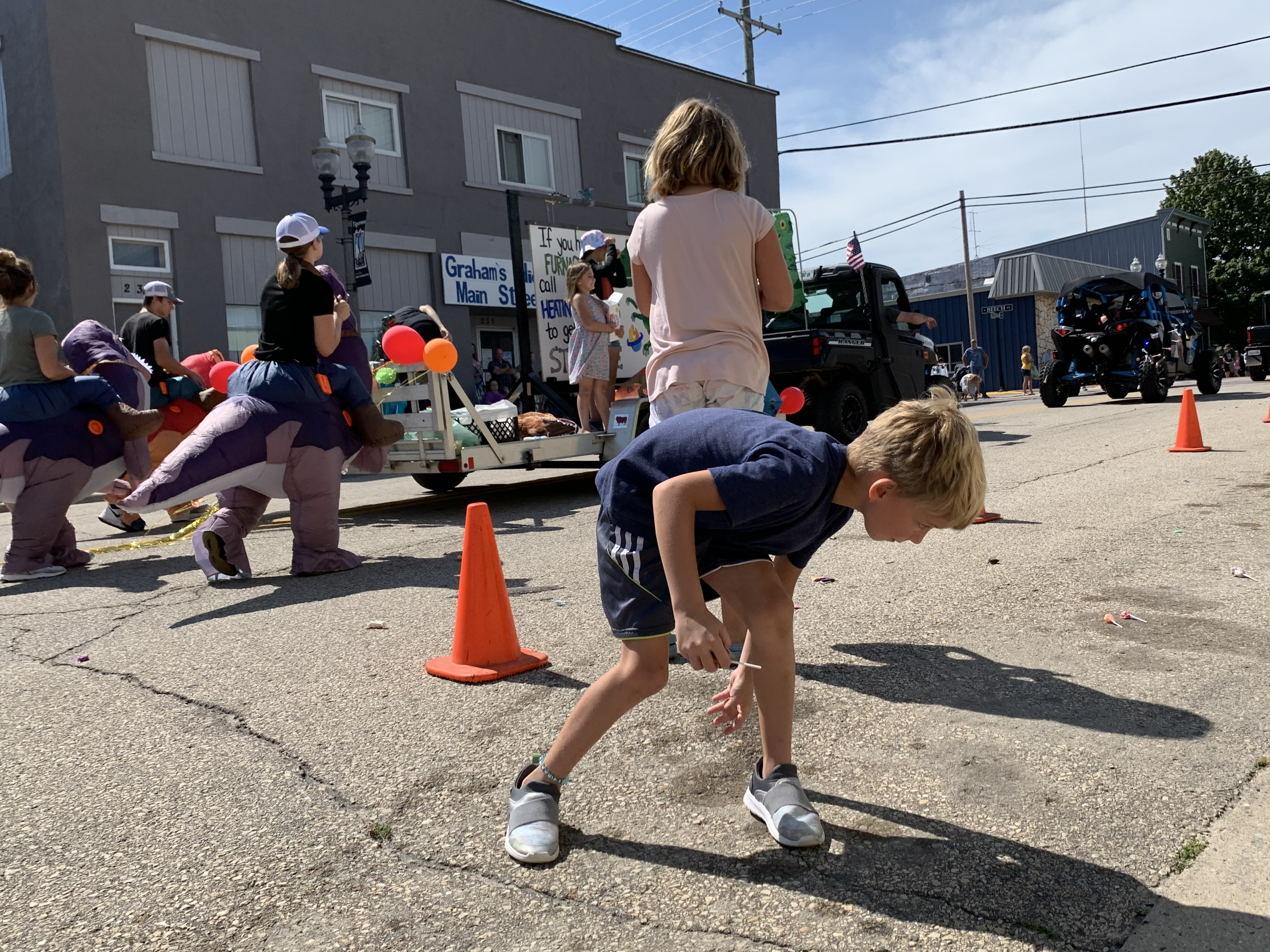 Neenah residents Remi Marta, front, and his sister Josie, back, race for candy as people in various floats toss it toward the crowd during the Lumberjack Days parade on Aug. 29.Luke Reimer | NEW Media