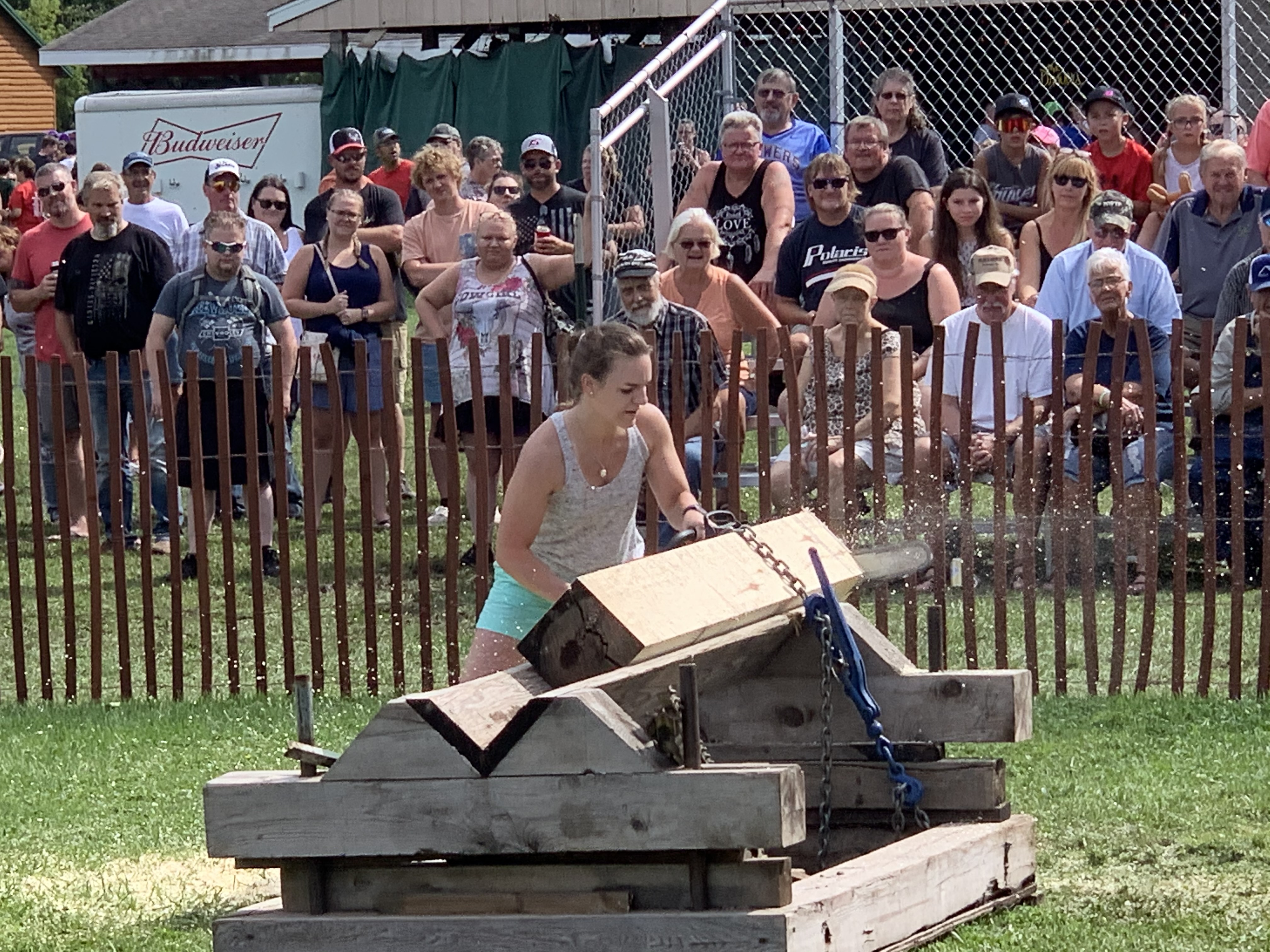 Dozens of spectators watch as Alison Stewart saws wood with a chainsaw during the Aug. 29 lumberjack competition at Legion Park.Luke Reimer | NEW Media