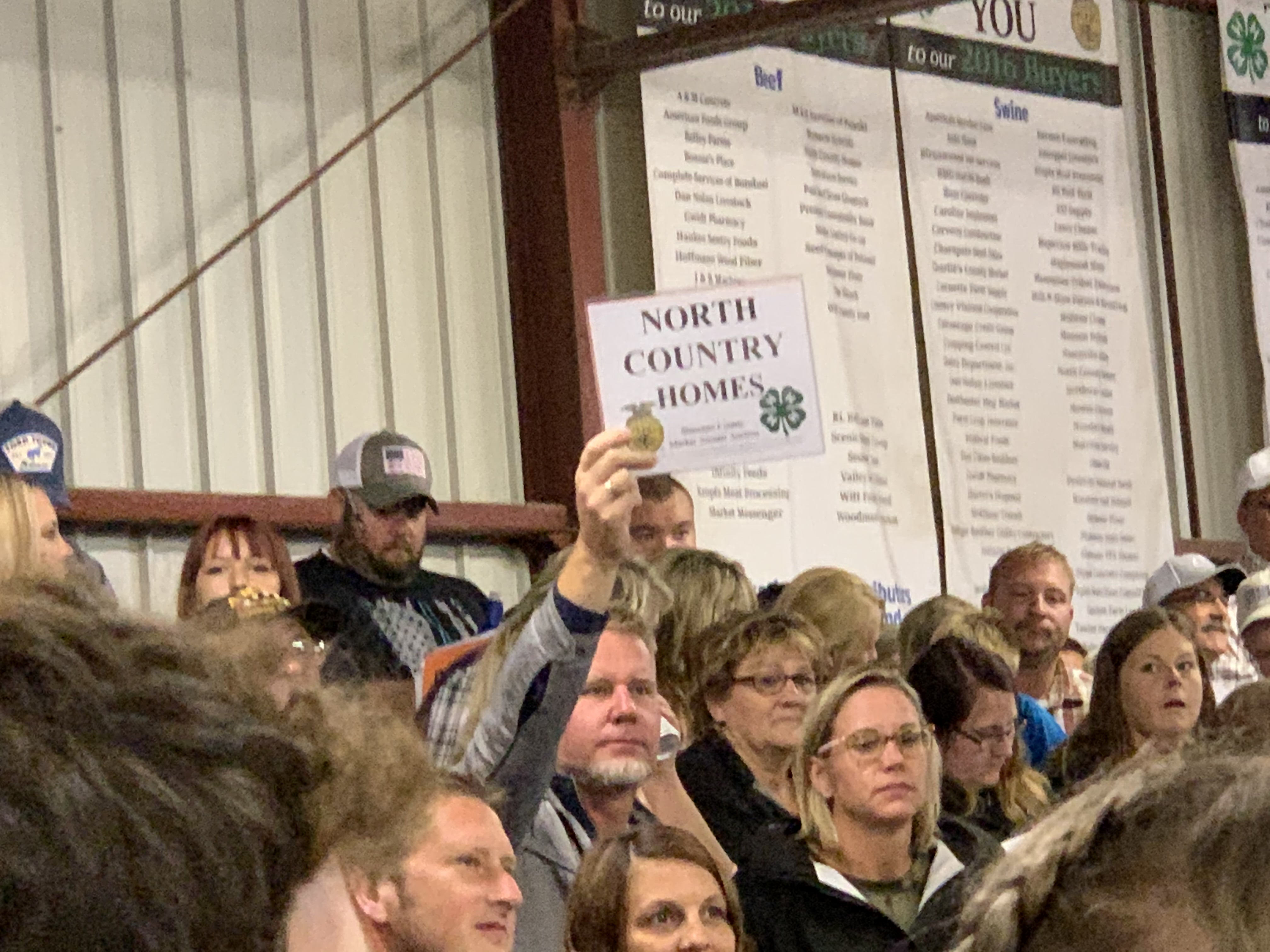 A representative from North Country Homes puts a bid in at the livestock auction at the Shawano County Fair on Sept. 3.<br />(Luke Reimer   NEW Media)