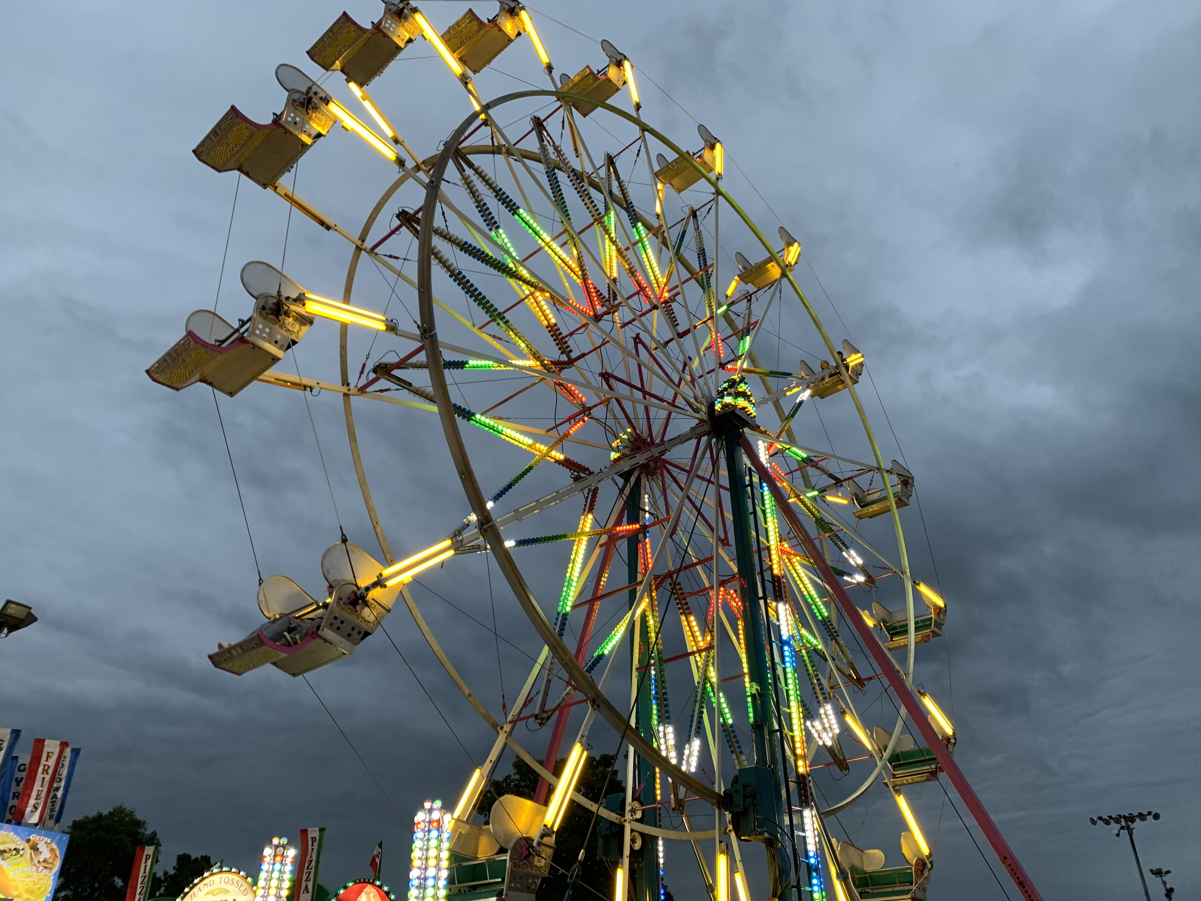 The ferris wheel brightens up the Shawano County Fairgrounds as dark clouds pass overhead on Sept. 3.<br />(Luke Reimer   NEW Media)