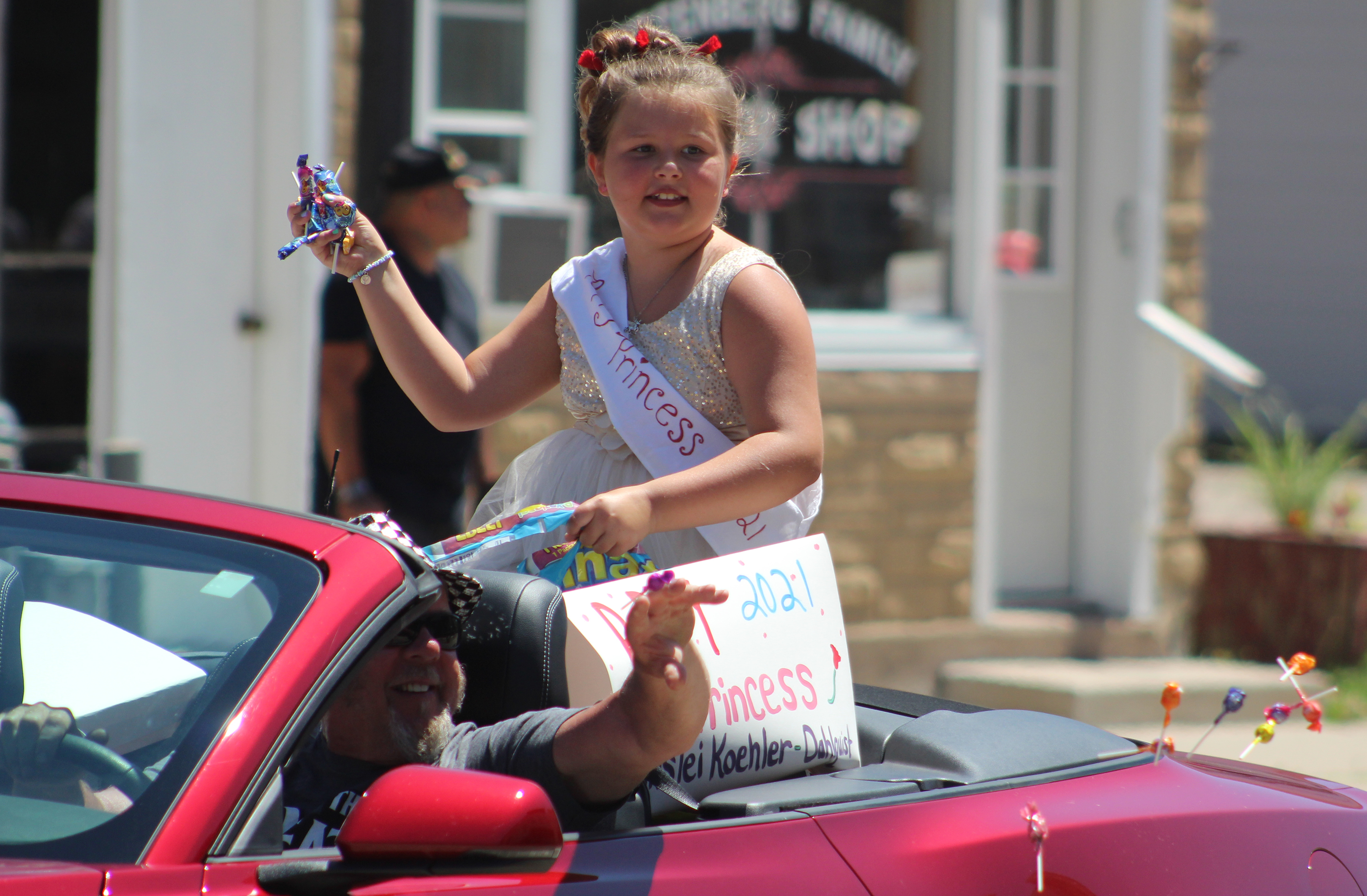 Kynslei Koehler-Dahlquist, the 2021 Poppy Princess, tosses candy June 13 to other children on the parade route during the Wittenberg Community Days parade.(Lee Pulaski   NEW Media)