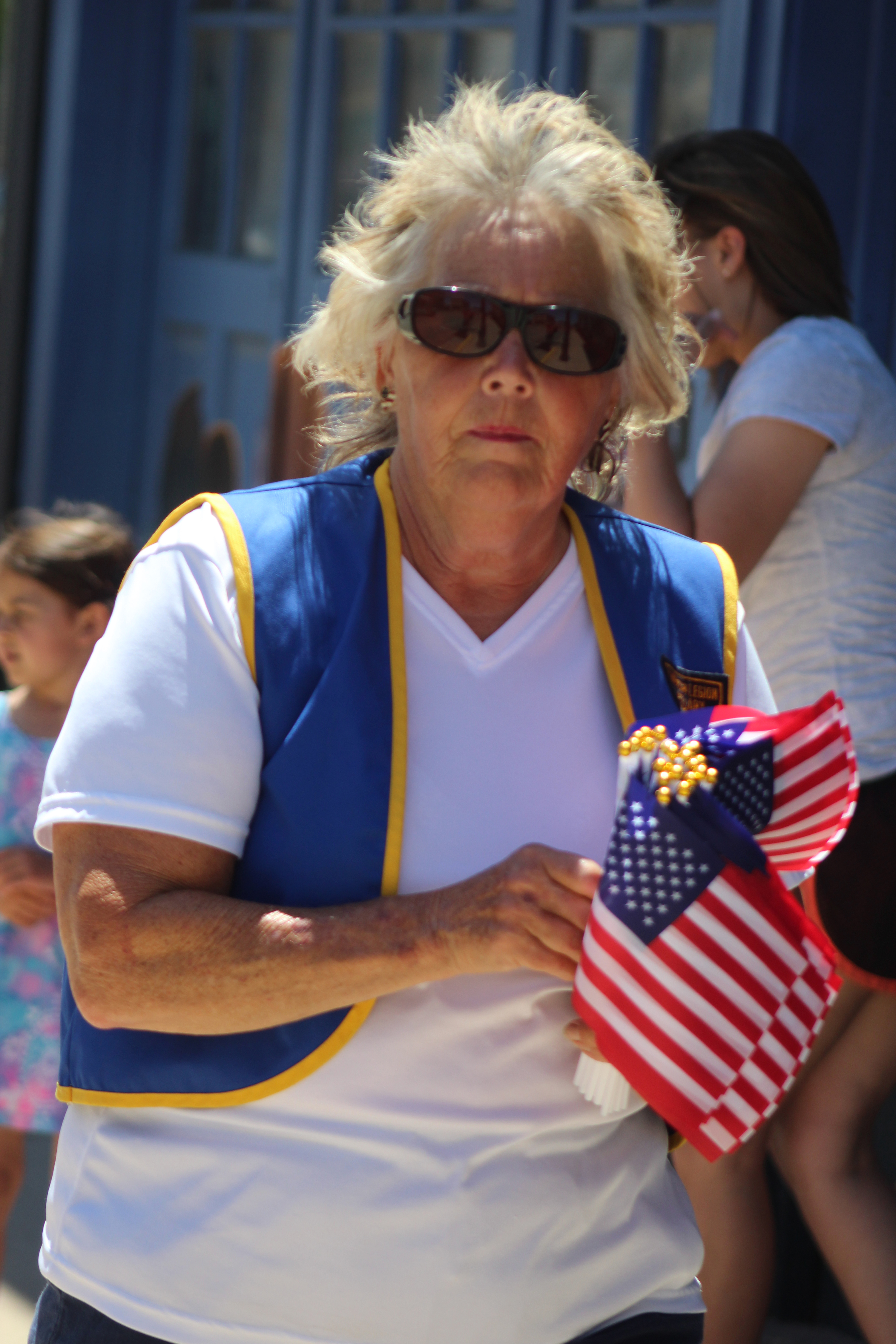 Rose Popp with American Legion Post 502 hands out American flags on the sidewalks in Wittenberg during the June 13 Wittenberg Community Days parade.(Lee Pulaski   NEW Media)