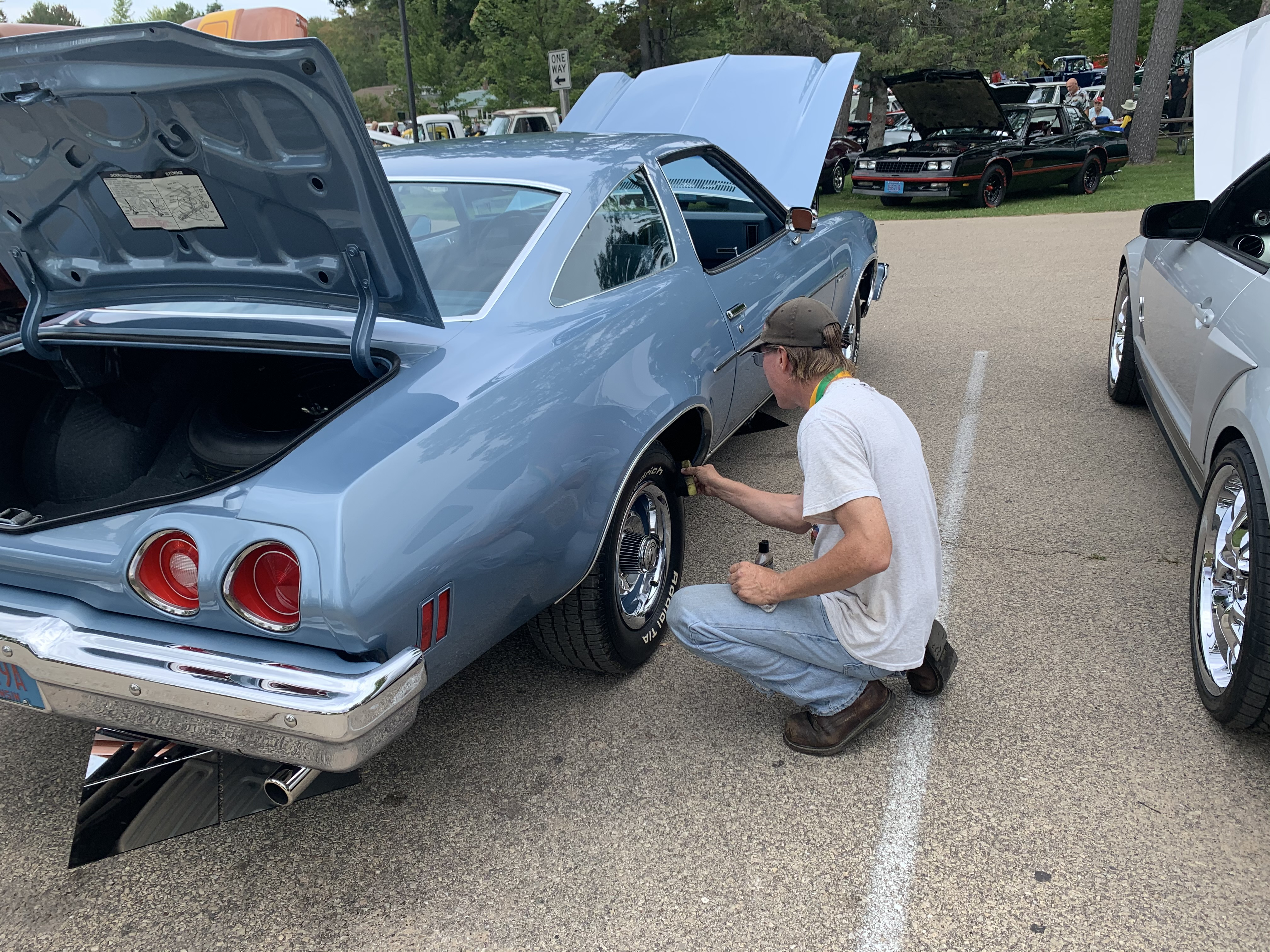 Oshkosh resident Jim Hibbert cleans his tires as a last-minute spruce-up during the car show at Shawano Lake County Park on Sept. 12.Luke Reimer | NEW Media