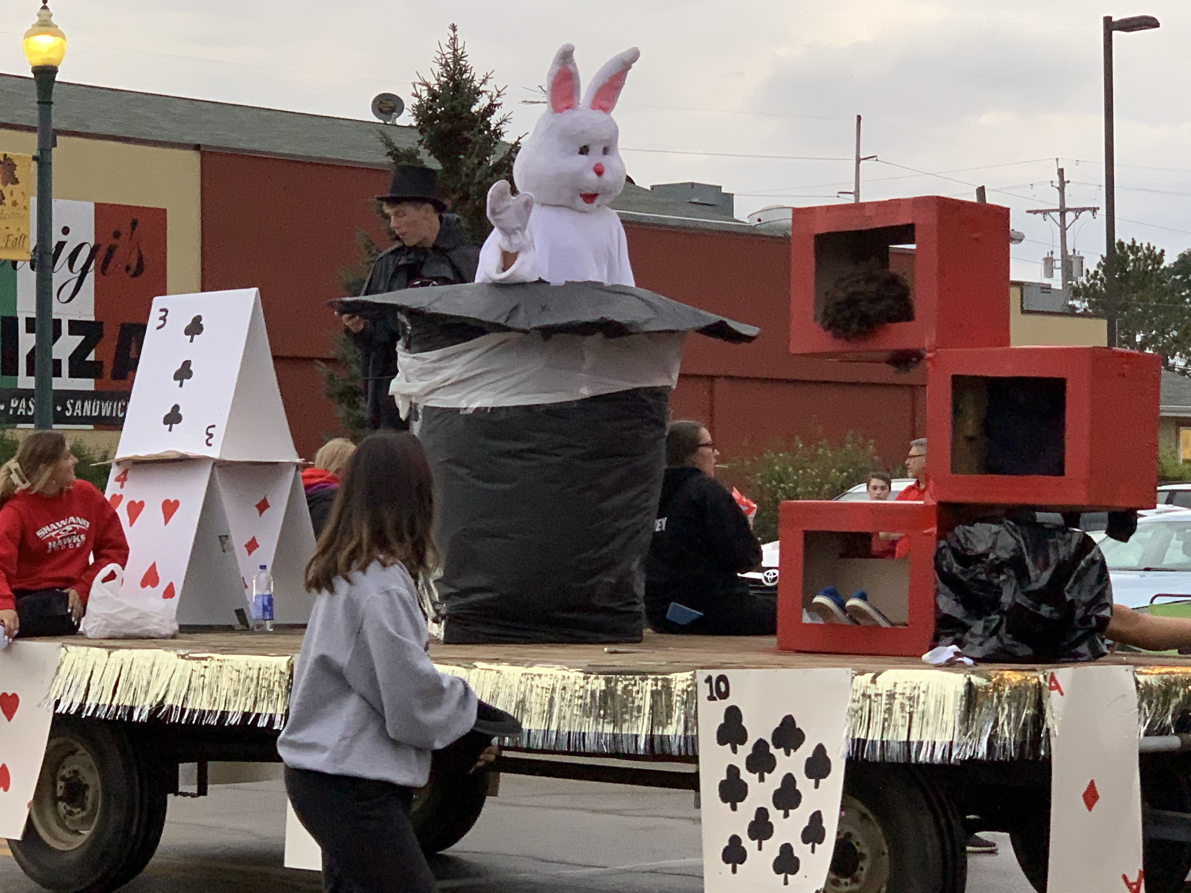 """To fit with the theme of """"magic happens,"""" a float travels down Main Street featuring playing cards and a human-sized rabbit coming out of a top hat during the homecoming parade on Sept. 24.Luke Reimer 