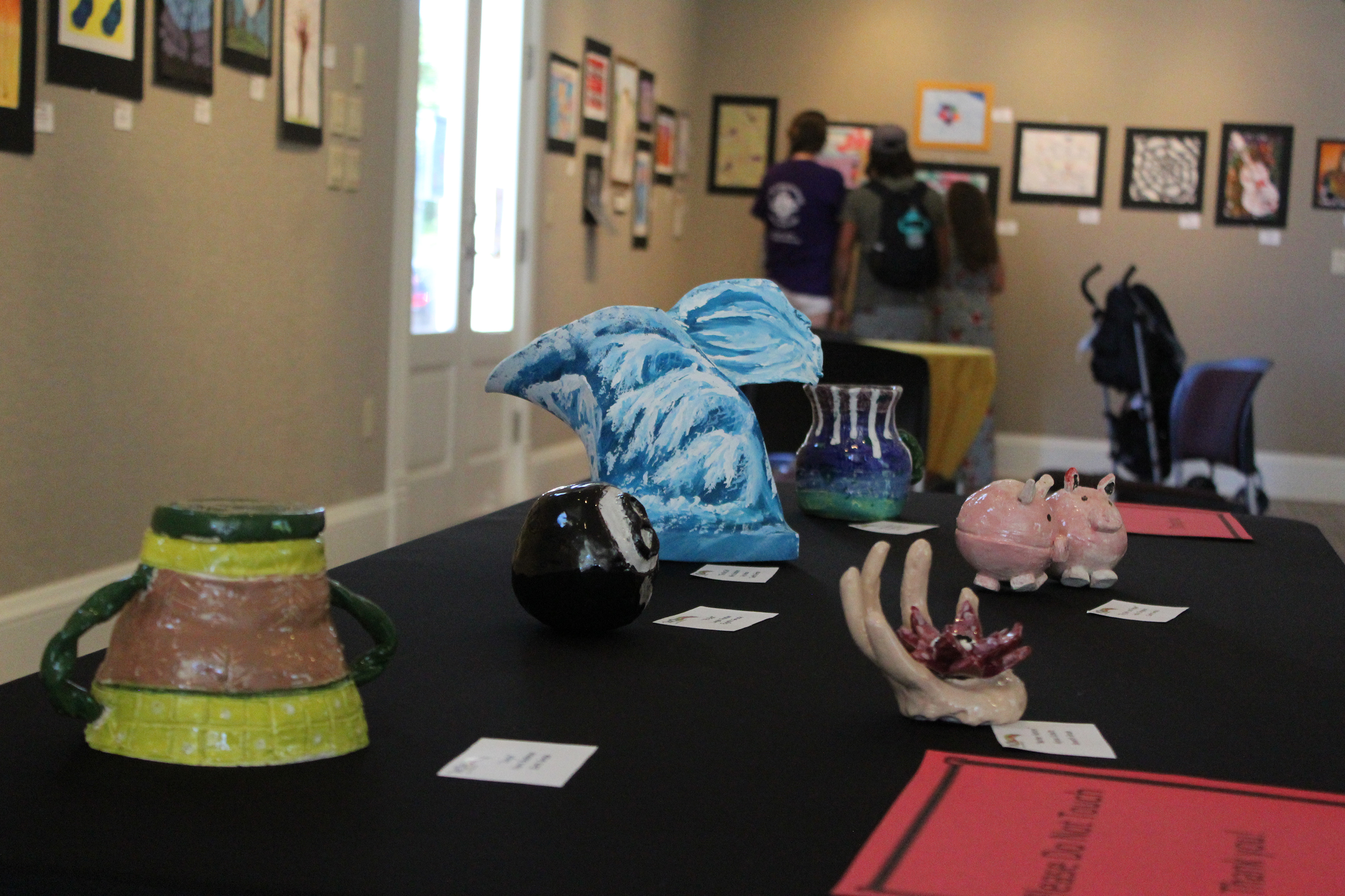 Assorted pieces of art done by students in the Wittenberg-Birnamwood School District sit on a table while patrons look at drawings and paintings on the wall June 13 at the WOWSPACE. The exhibit, featuring young artists, concluded with Wittenberg Community Days.(Lee Pulaski   NEW Media)
