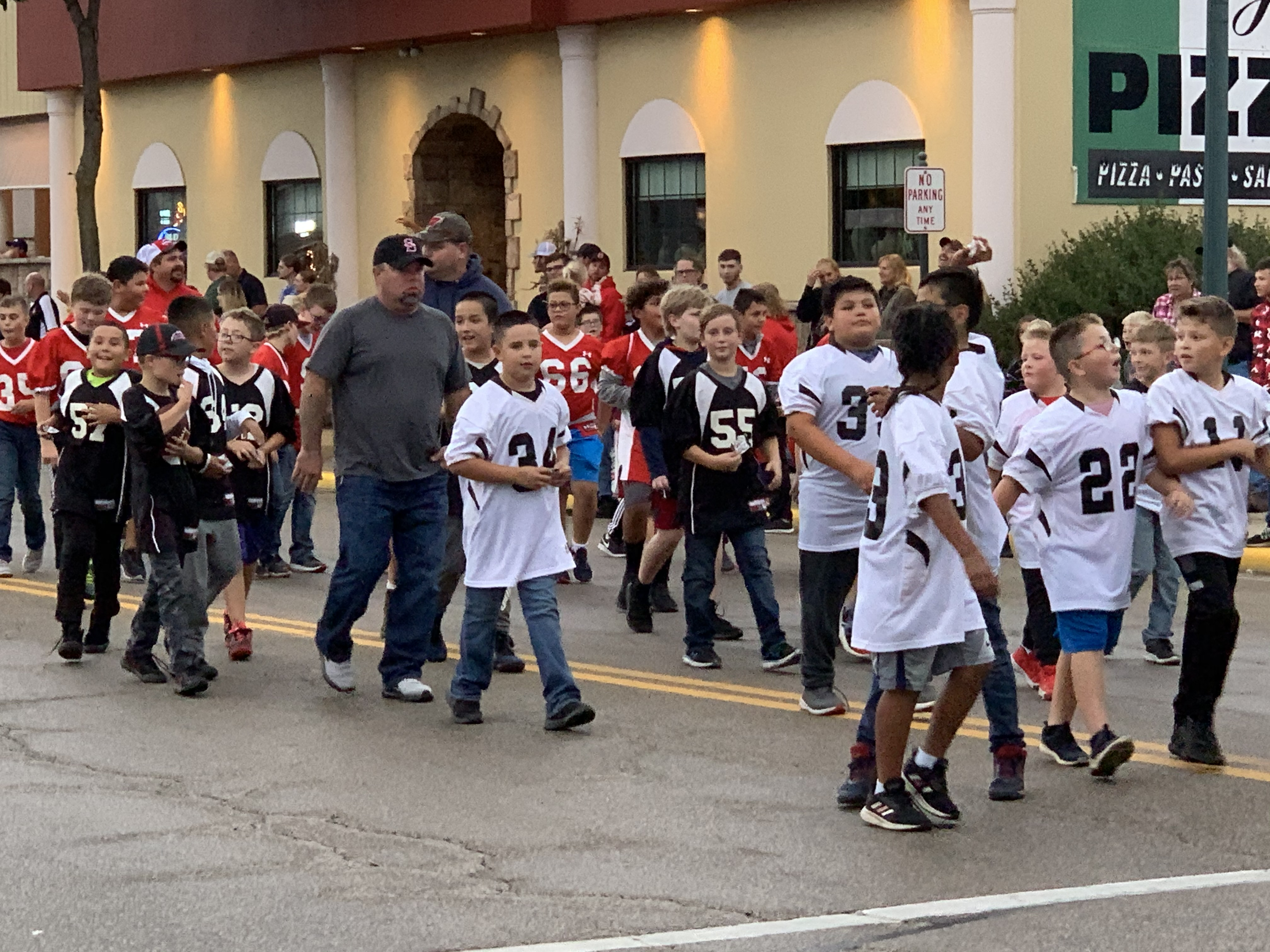 Children involved with youth football get their chance to wave to Shawano visitors as they walk down Main Street during the homecoming parade on Sept. 24.Luke Reimer | NEW Media