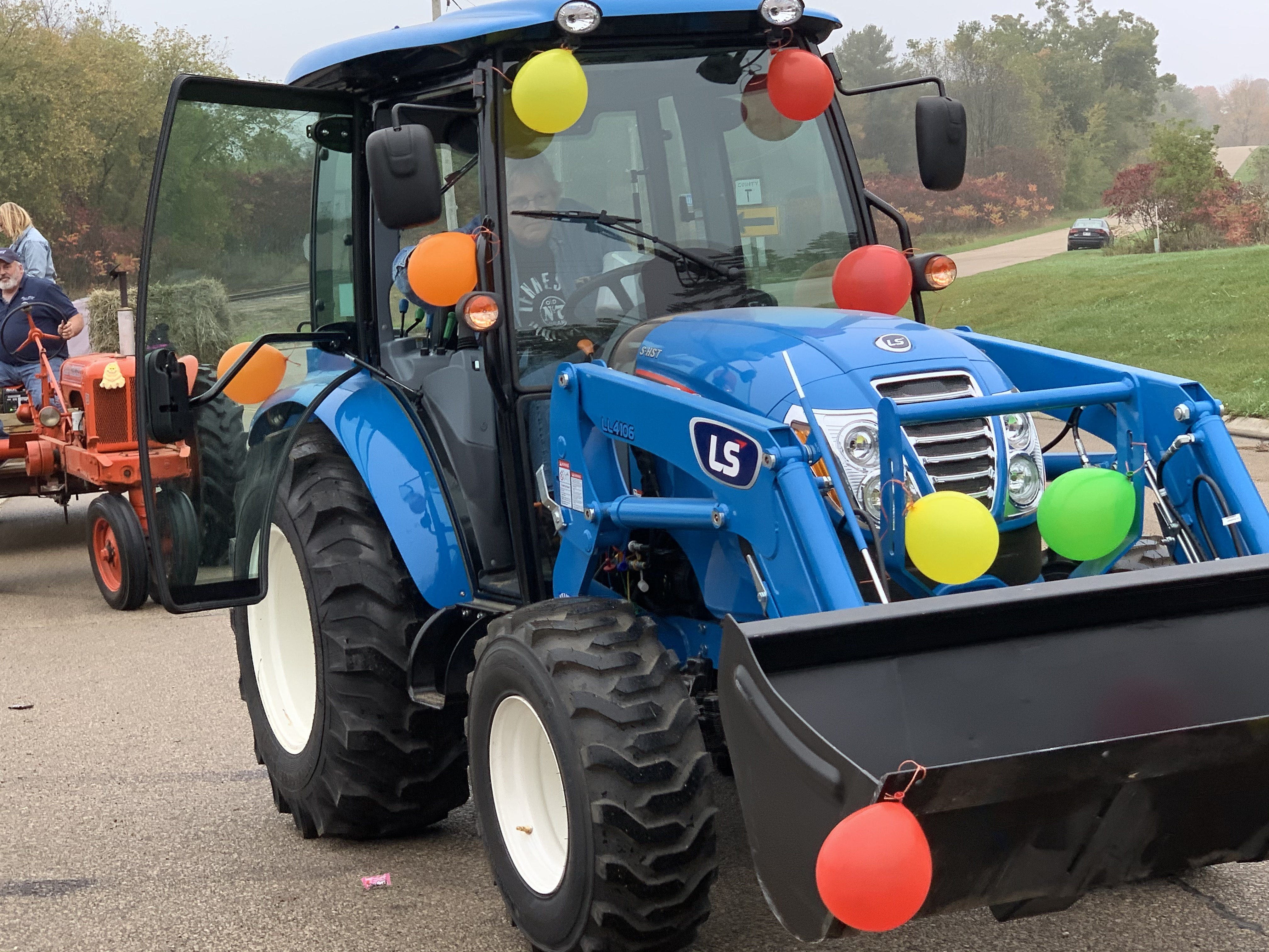 A blue tractor decorated with balloons rolls down County Road T in Lunds, part of the Bohemian Fest parade Oct. 9.Luke Reimer   NEW Media