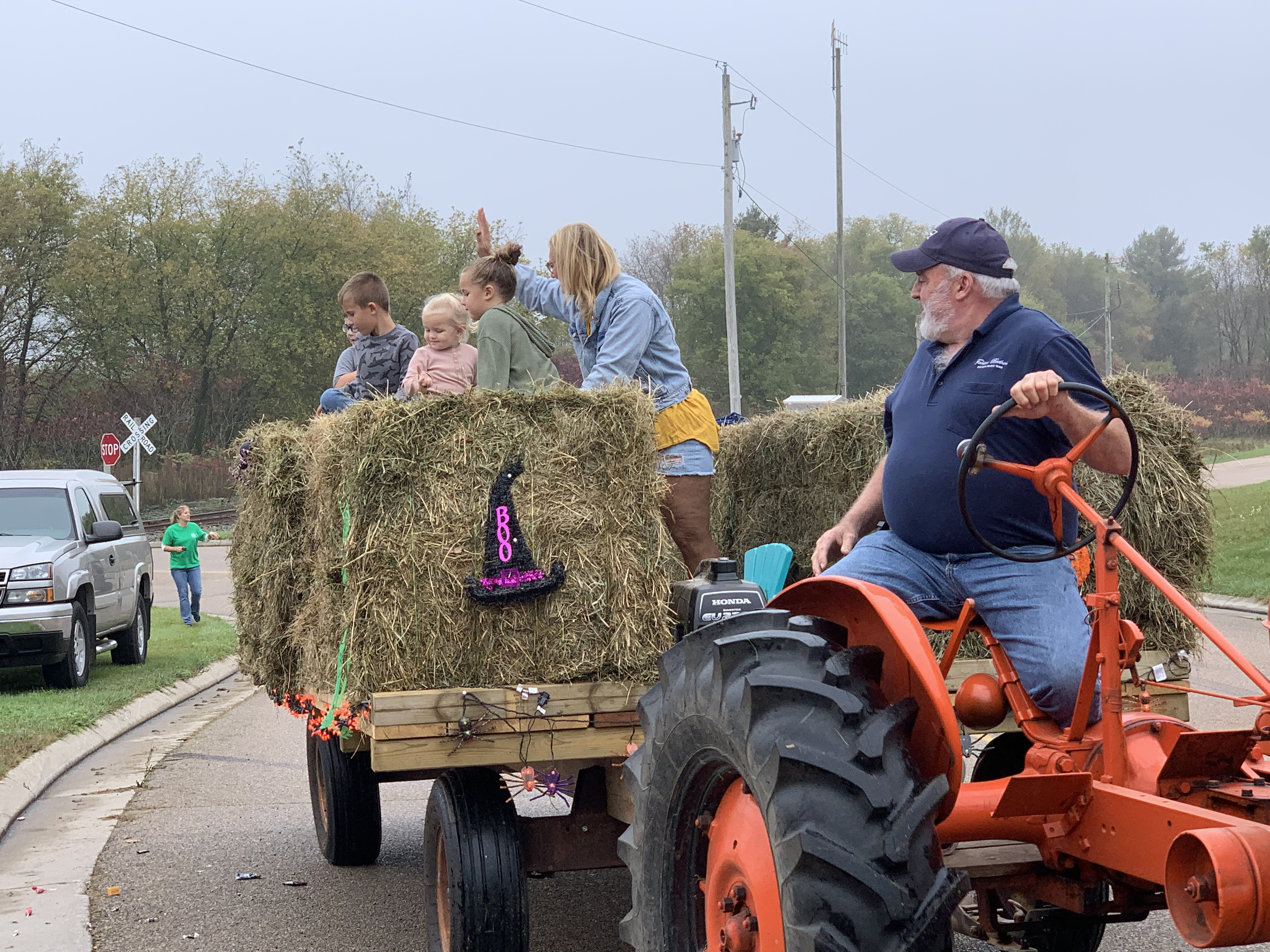 Children ride on hay bales behind a tractor as they wave to visitors and throw candy on County Road T in Lunds on Oct. 9.Luke Reimer   NEW Media