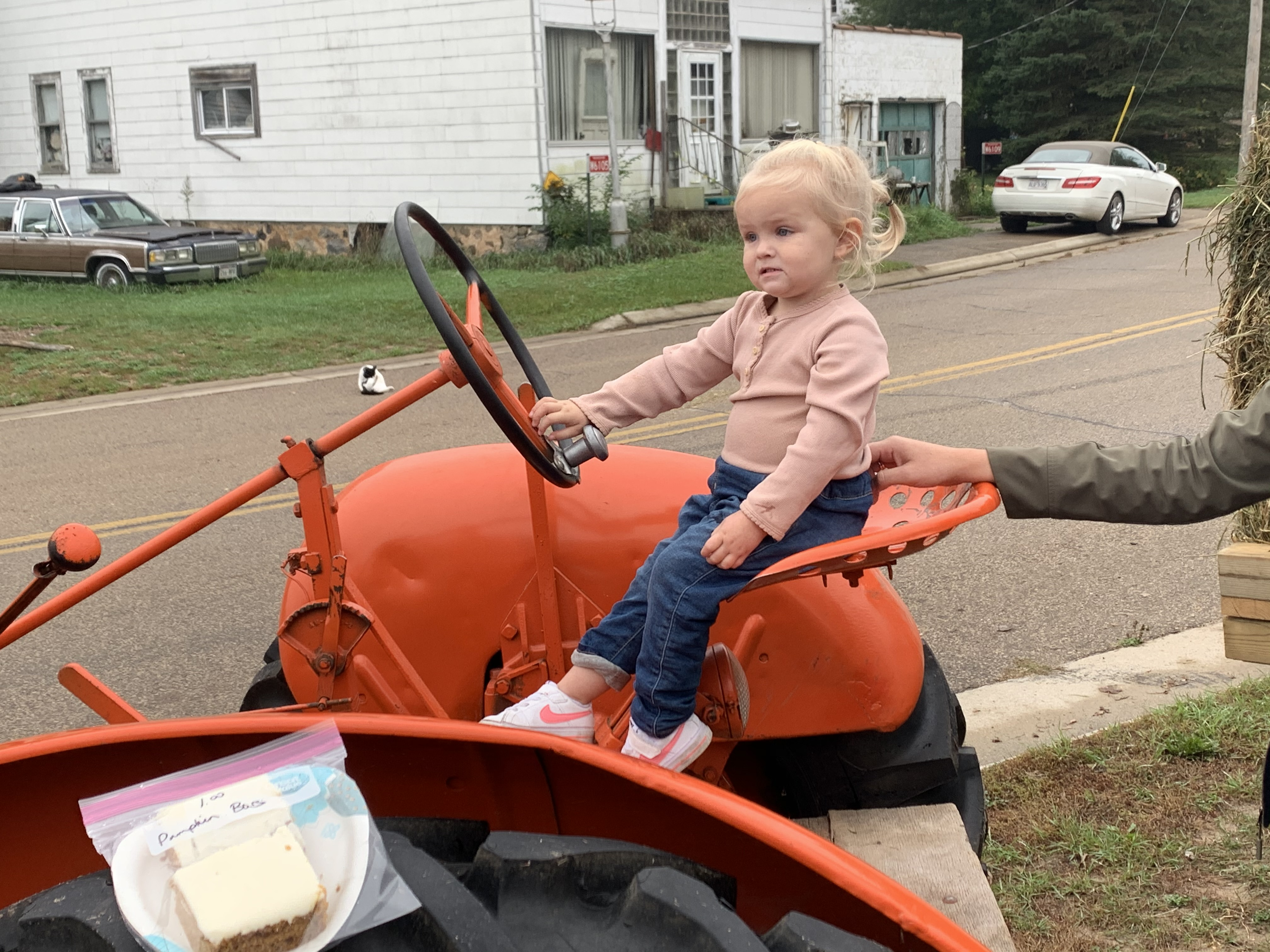 Shawano resident Noella Coe sits in the driver seat of a tractor, pretending that she is driving down the street at Bohemian Fest on Oct. 9 in Lunds. The event included a parade and lunch.Luke Reimer   NEW Media