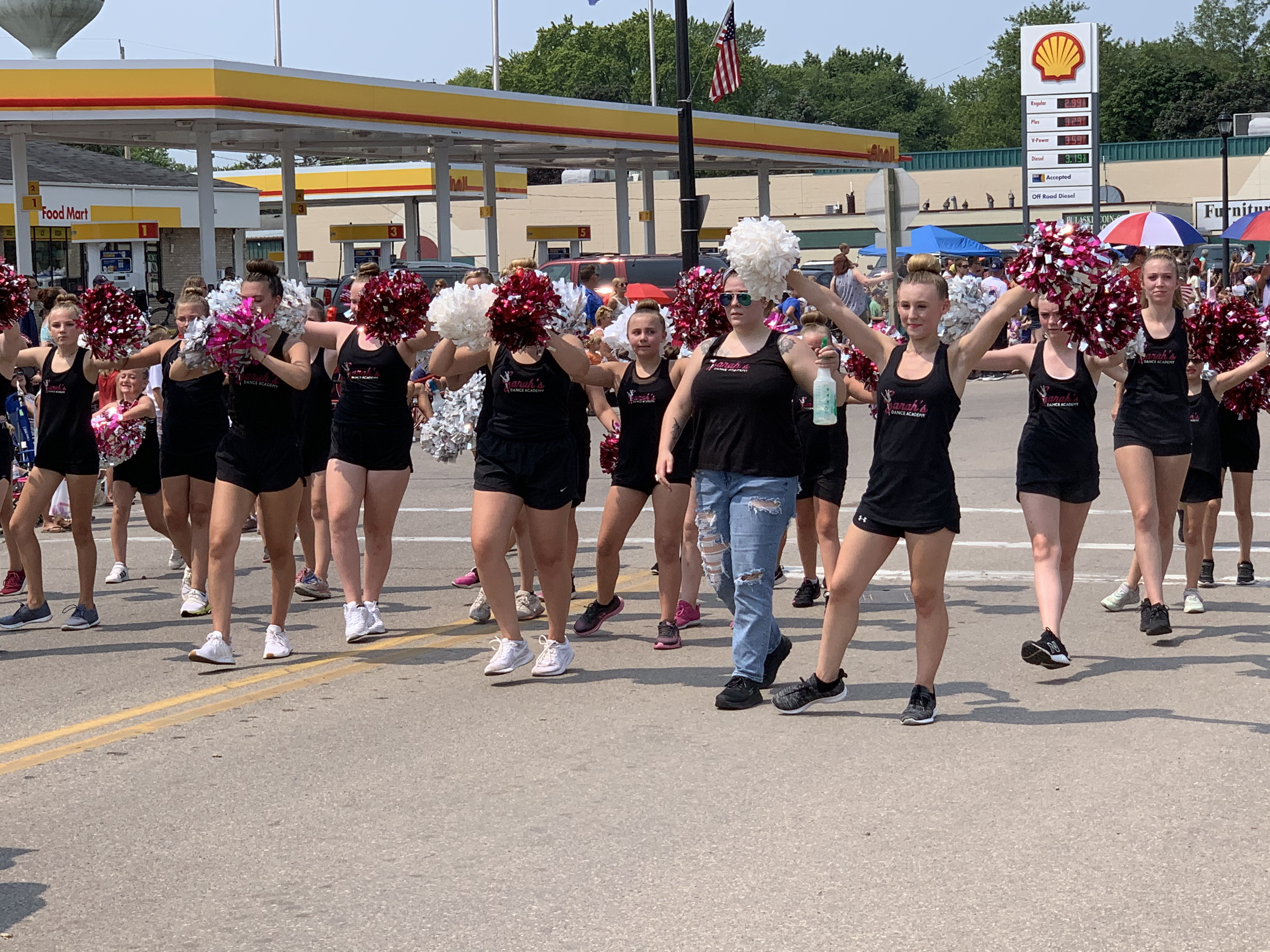 Members of Sarah's Dance Academy perform dances with their pom-poms as they walk down Pulaski Street on July 18.Luke Reimer   NEW Media