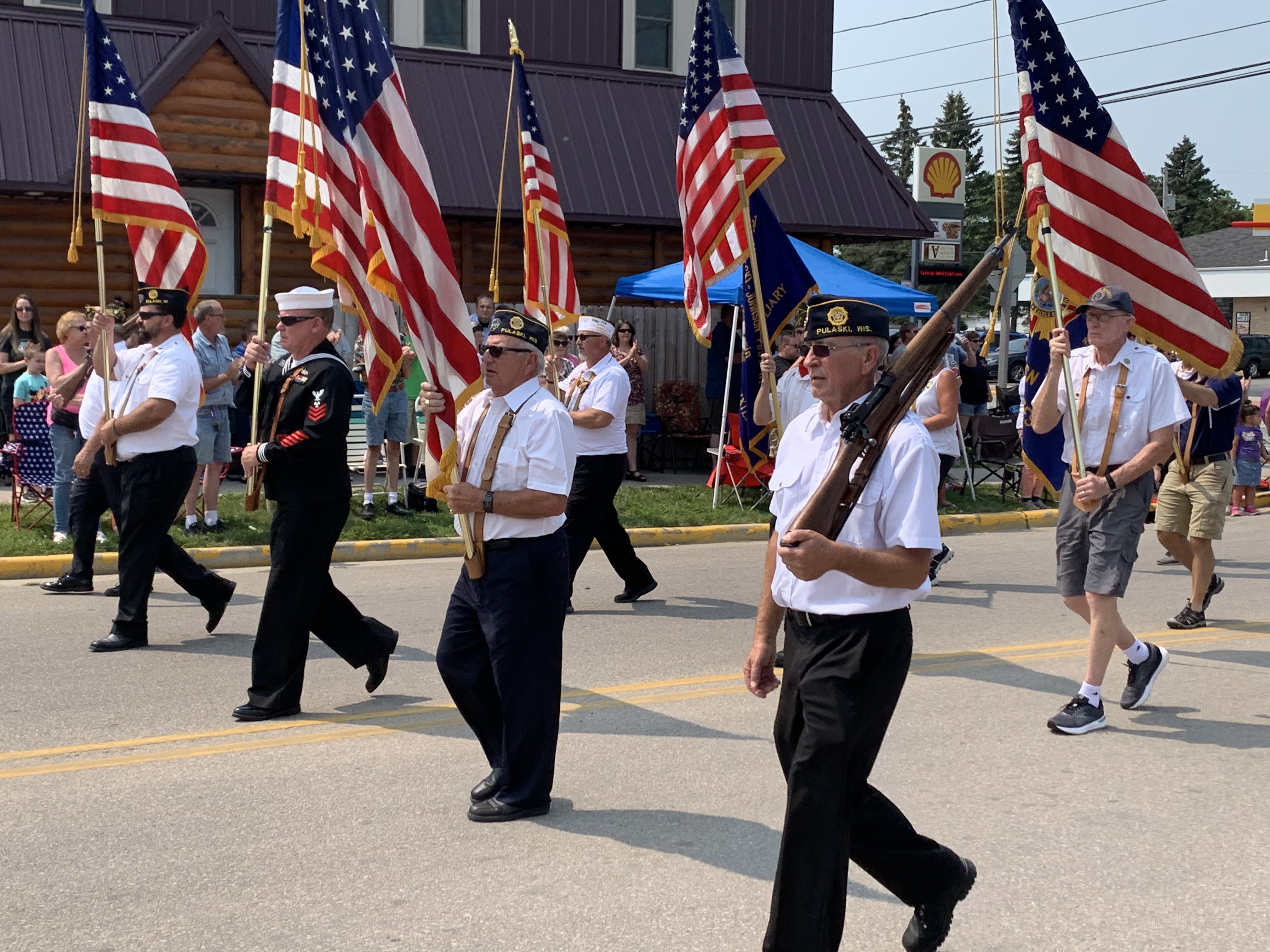 Members of the American Legion kick off the parade by walking flags down Pulaski Street on July 18.Luke Reimer   NEW Media