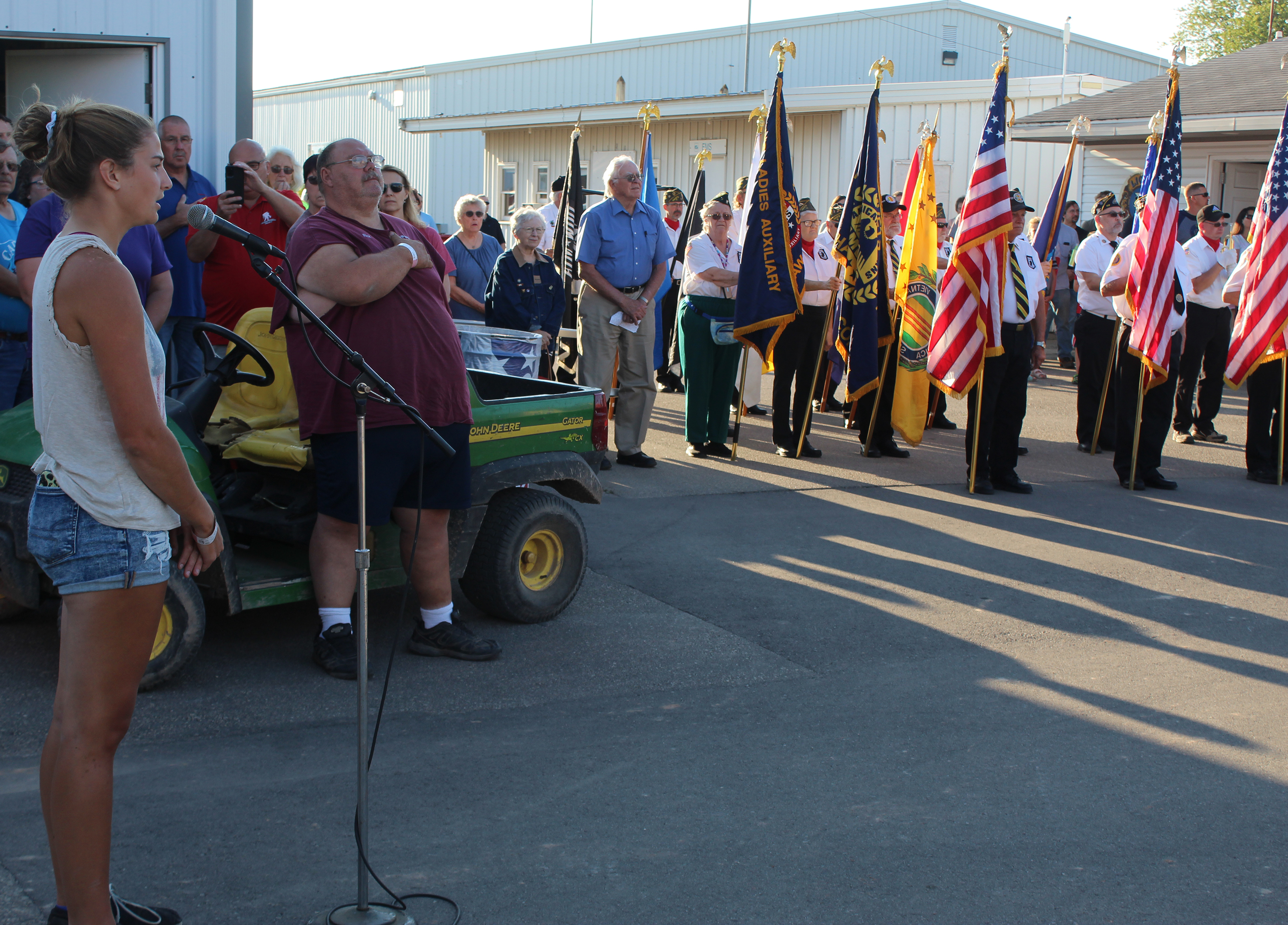 """Brooke Breitrich sings """"Star-Spangled Banner"""" at the opening ceremony for the Shawano County Fair on Sept. 1 as the color guard stands at attention and members of the crowd put their hands on their hearts.<br />(Lee Pulaski   NEW Media)"""