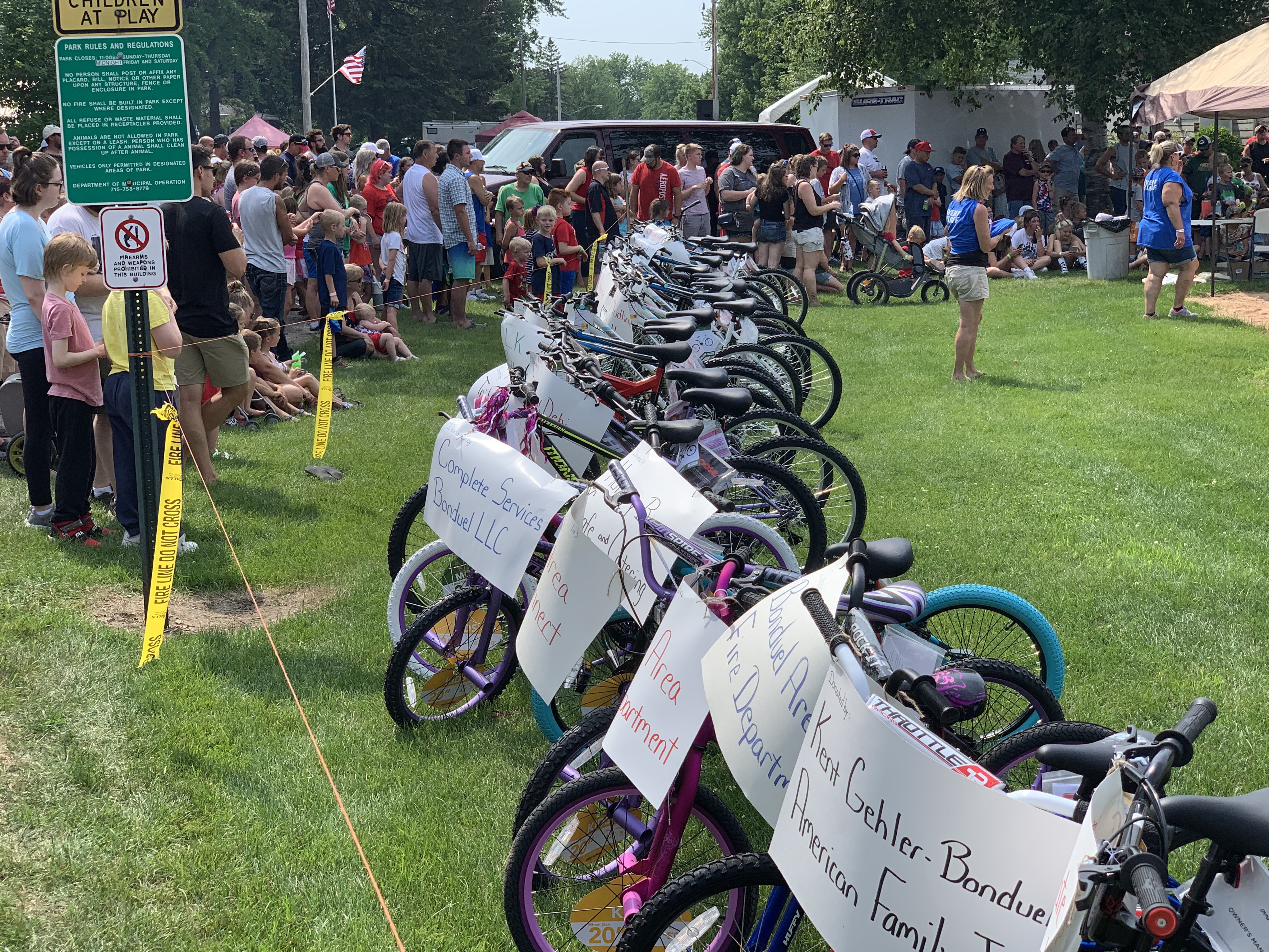 Visitors wait in anticipation of the bike raffle July 4 at Village Park in Bonduel. More than 100 bikes were donated for families to win at the event.Luke Reimer | NEW Media
