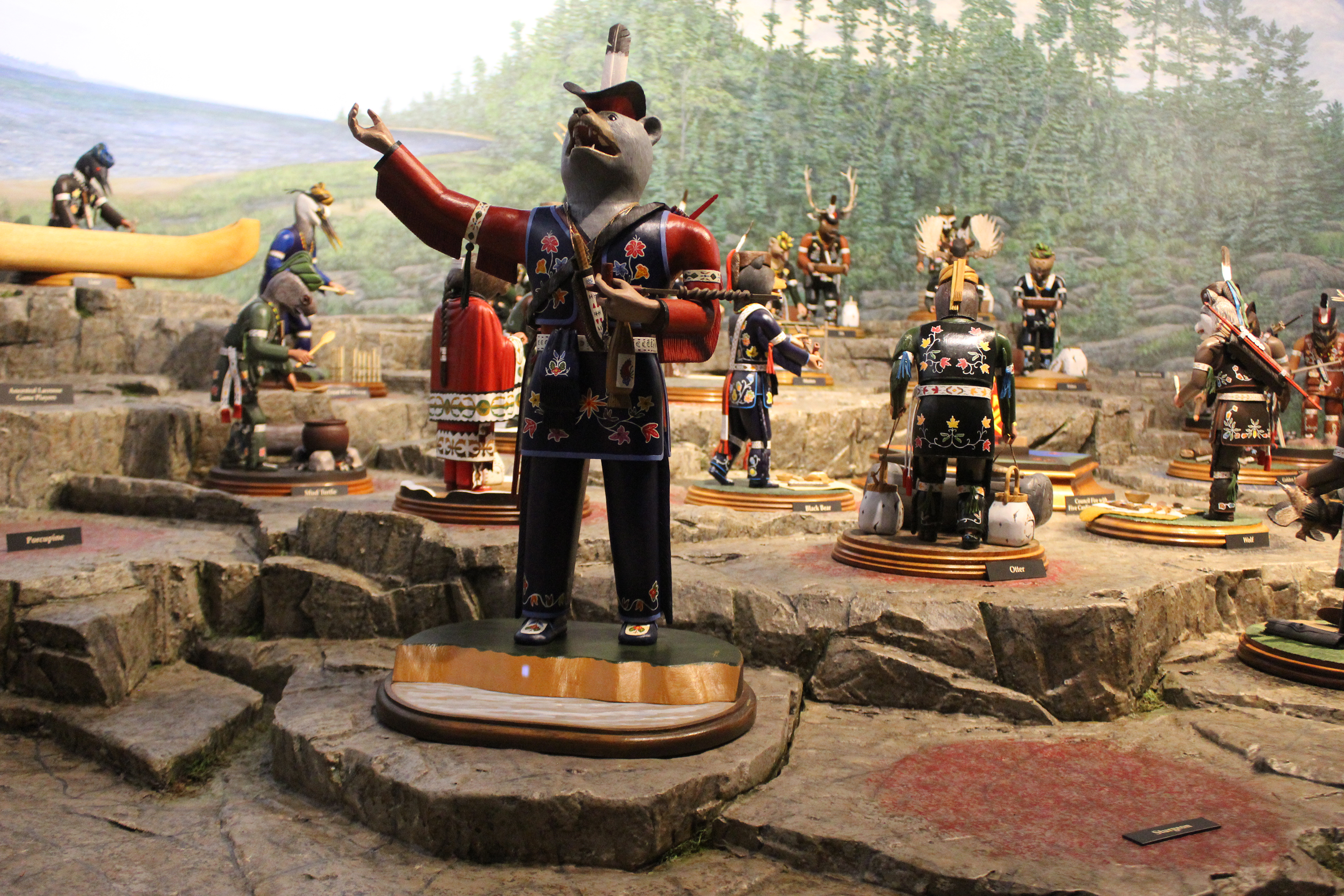 A bear figure reaches outward while others look inward toward a ceremonial fire at the Menominee Clans Story exhibit currently on display at Oshkosh Public Museum.(Lee Pulaski   NEW Media)