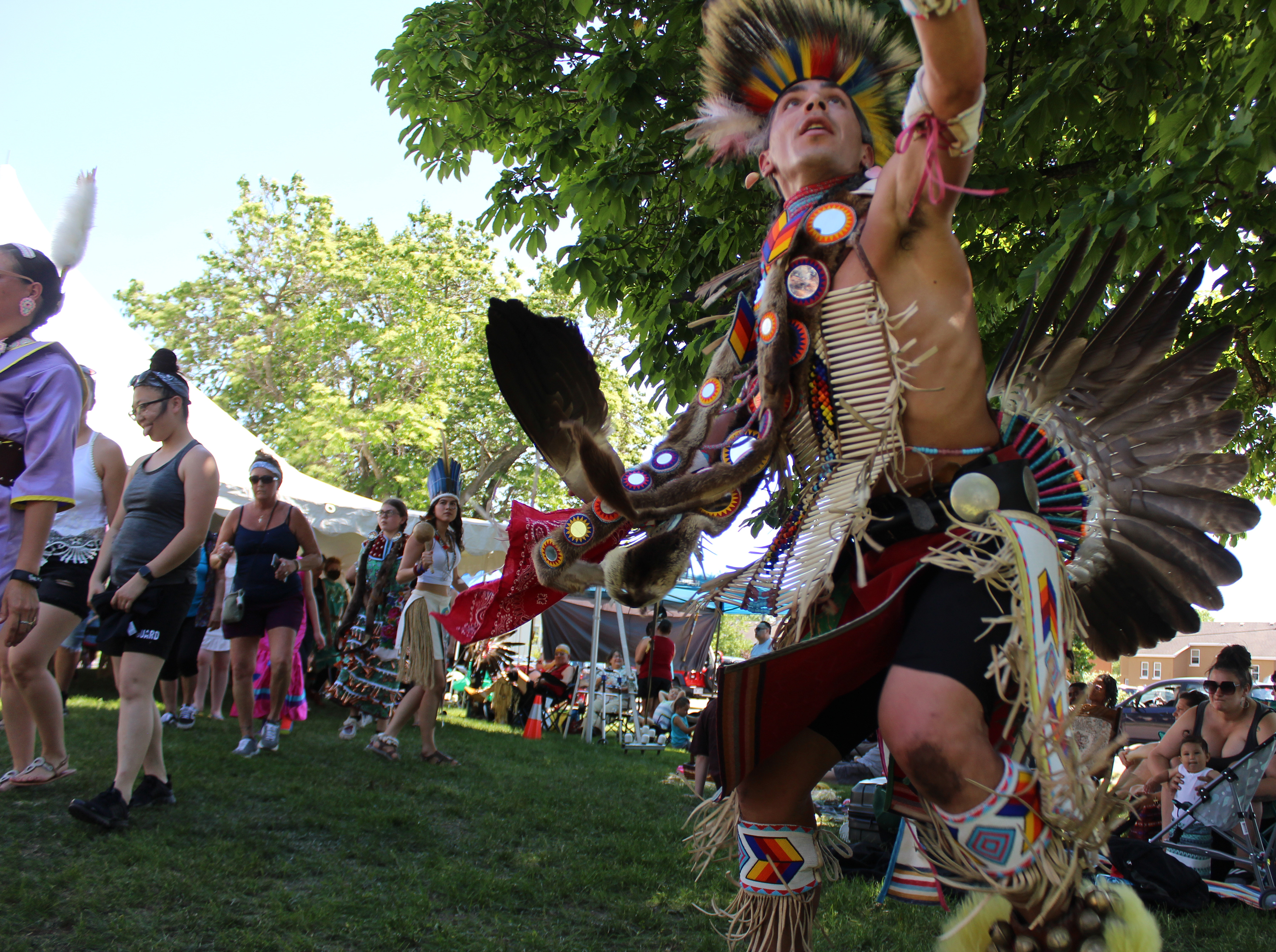 Josh Zunker, a Ho-Chunk tribal member from Weston, reaches for the sky as other dancers move around the arena June 5 outside the Oshkosh Public Museum.(Lee Pulaski   NEW Media)