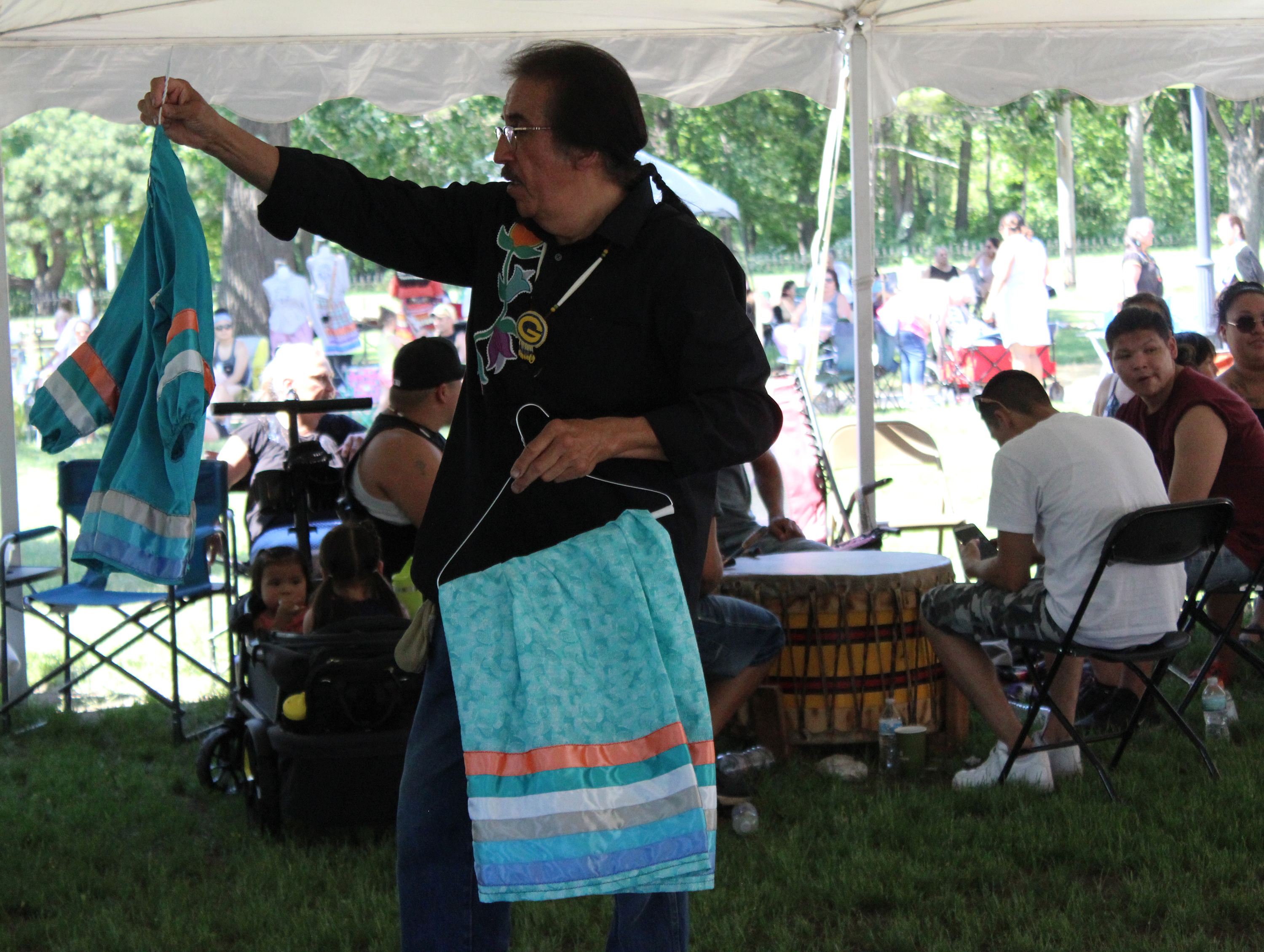 Gary Besaw with the Menominee Tribal Legislature shows off a donated outfit that was later given as a prize during the powwow June 5 at Oshkosh Public Museum.(Lee Pulaski   NEW Media)