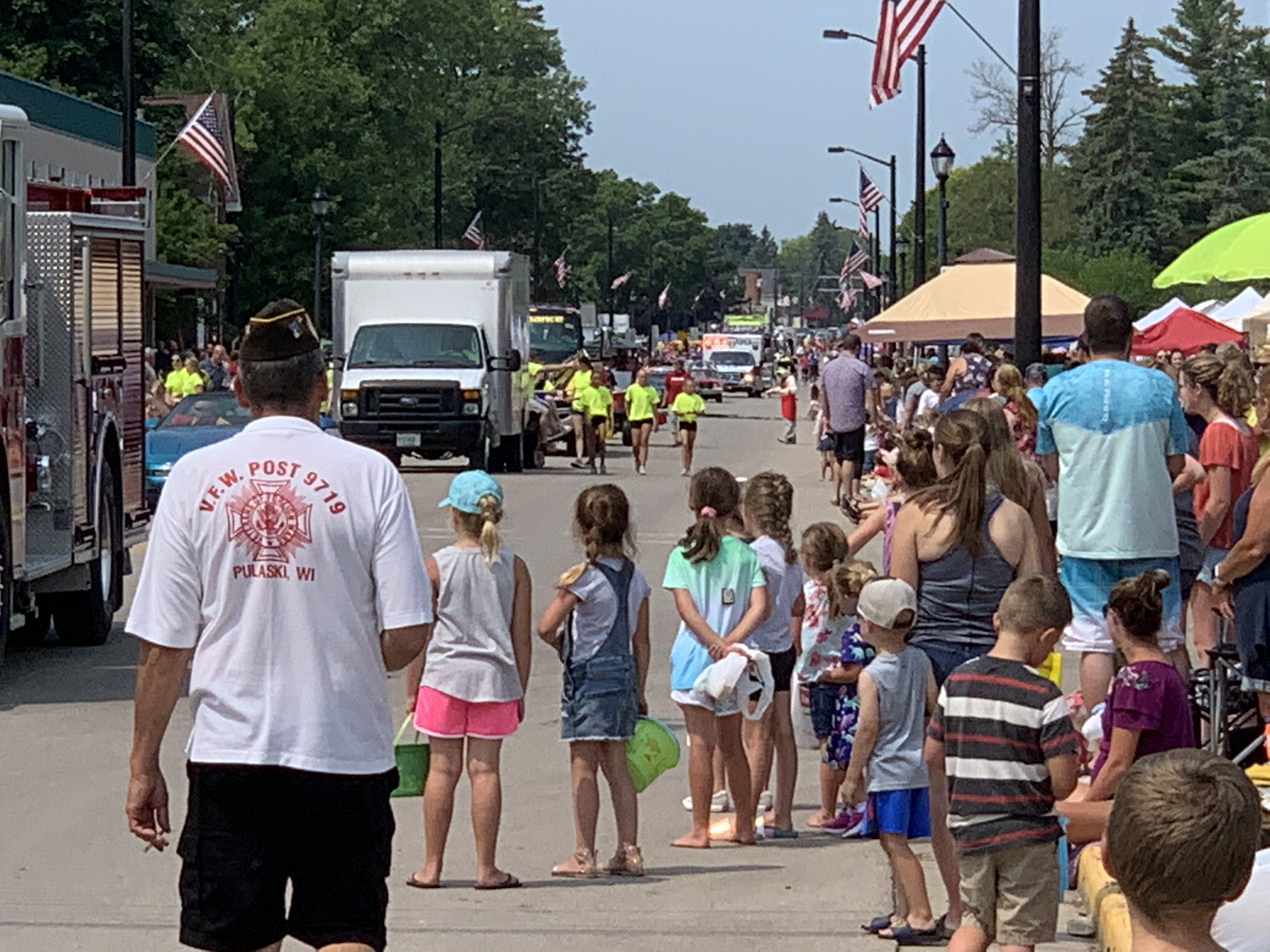 Both children and adults wait in anticipation for candy and to see the floats as they drive down Pulaski Street on July 18.Luke Reimer   NEW Media