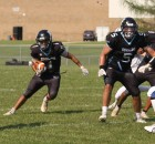 Menominee Indian's Allen Smith, left, looks for a lane to run through as teammate Wendell Waukau Jr. provides blocking during the team's nonconference game against Auburndale on Aug. 19 in Keshena. The Eagles' offense struggled to move the ball in a 48-0 season-opening loss.  Morgan Rode | NEW Media