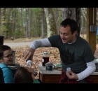 Presenter Kyle Beach gives 8-year-old Everett Rolfing an up close and personal taste of freshly processed maple syrup during the annual Maple Festival at YMCA Camp U-Nah-Li-Ya on April 10, to the delight of his sister, Malia. Warren Bluhm | NEW Media