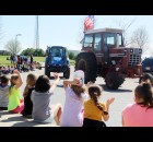 Students at Hillcrest Primary School wave excitedly April 16 as tractors driven by Shawano FFA members roll through Hillcrest's parking lot in a parade. The event was part of the Drive Your Tractor to School Day event. (Lee Pulaski | NEW Media)