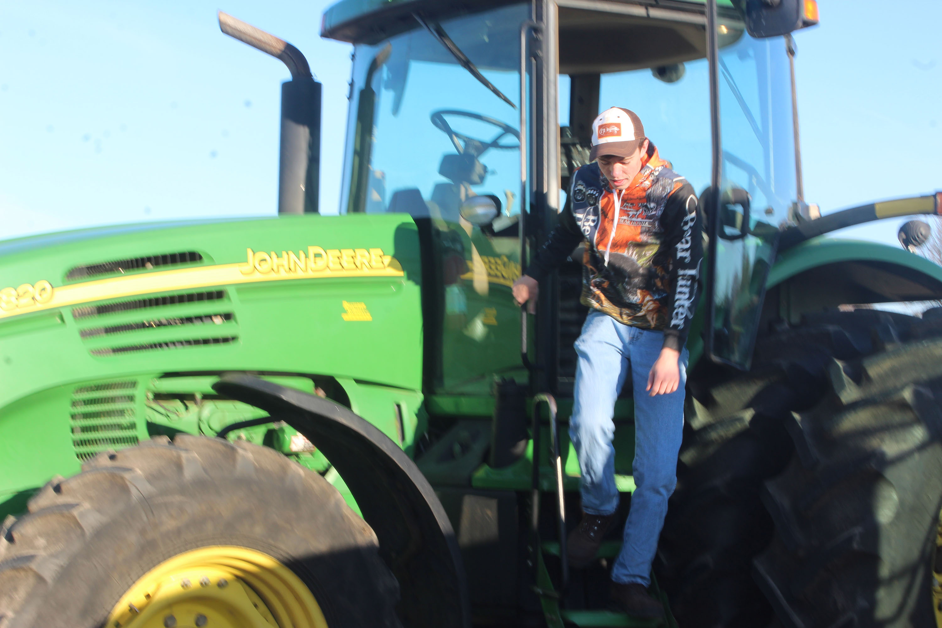 Shawano Community High School senior John Rhode climbs out of his family's John Deere tractor April 17 in the high school's parking lot. Rhode was one of almost a dozen members of the Shawano FFA who drove their tractors to school.<br />(Lee Pulaski | NEW Media)
